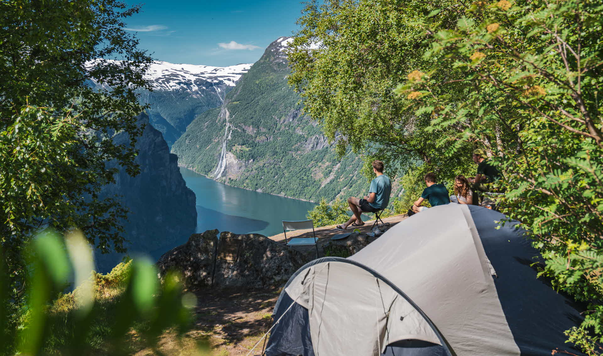 A tent and four campers on a cliff above Geirangerfjord