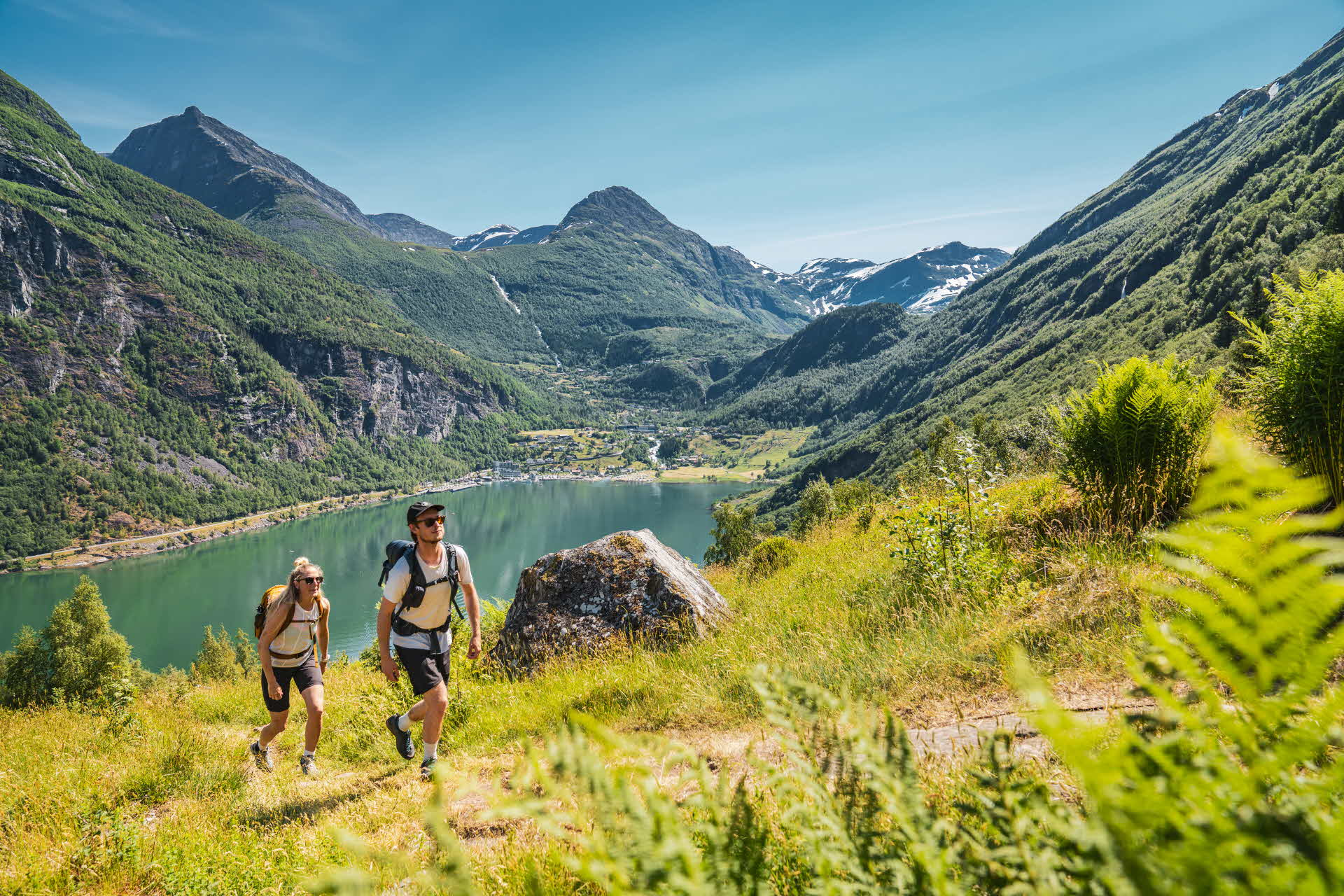 A man and woman hiking with Geiranger and Geirangerfjord in the background