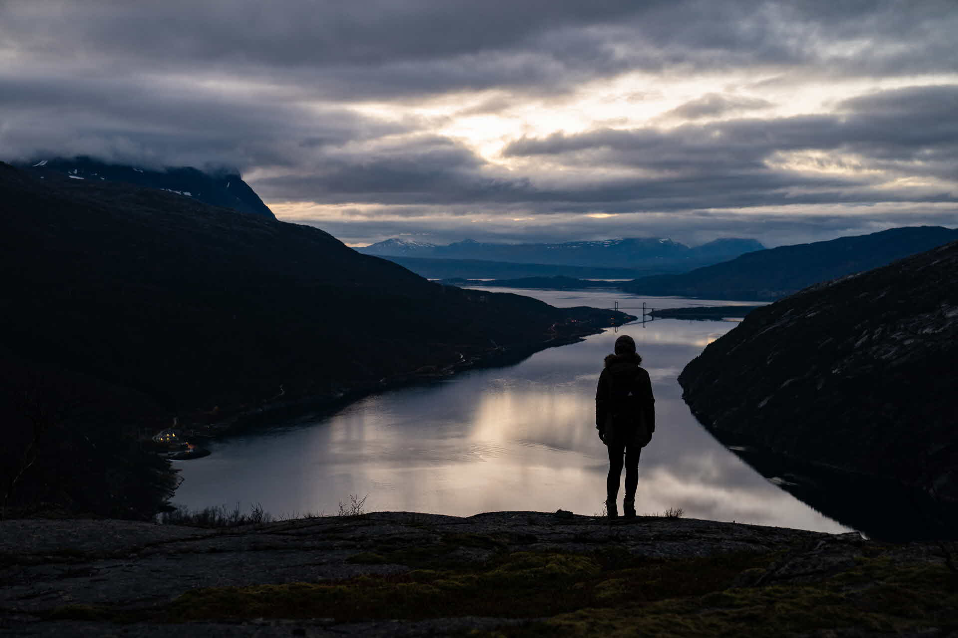 The silhouette of a woman as she stands on top of mountain late night by the Ofot railway overlooking the Rombakfjord