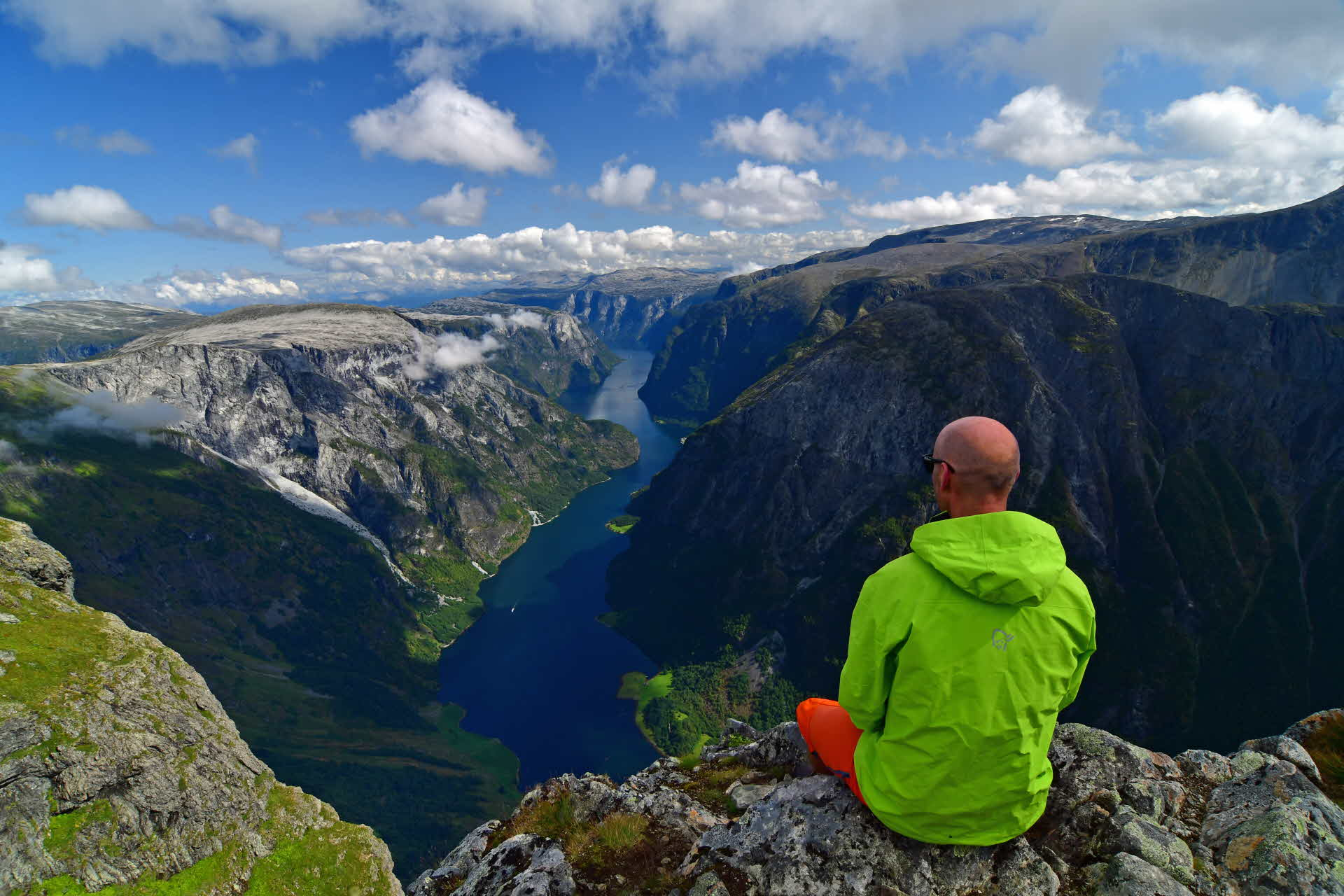 A man sitting at the top of Bakkanosi over the Nærøyfjord
