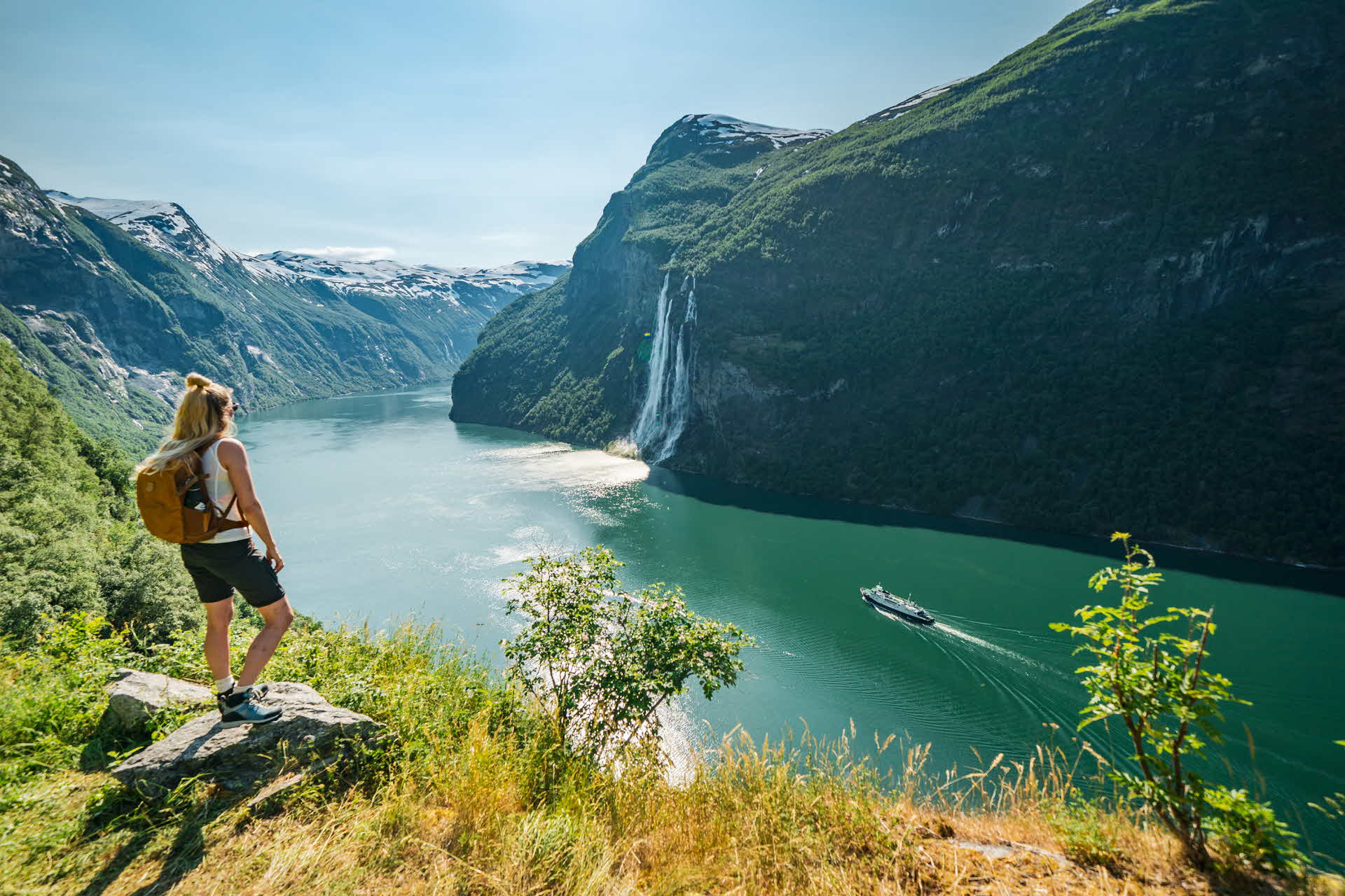 A woman looking down on the Geirangerfjord while hiking