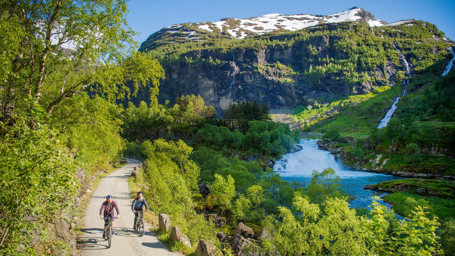 Two cyclists by the river in Flåmsdalen