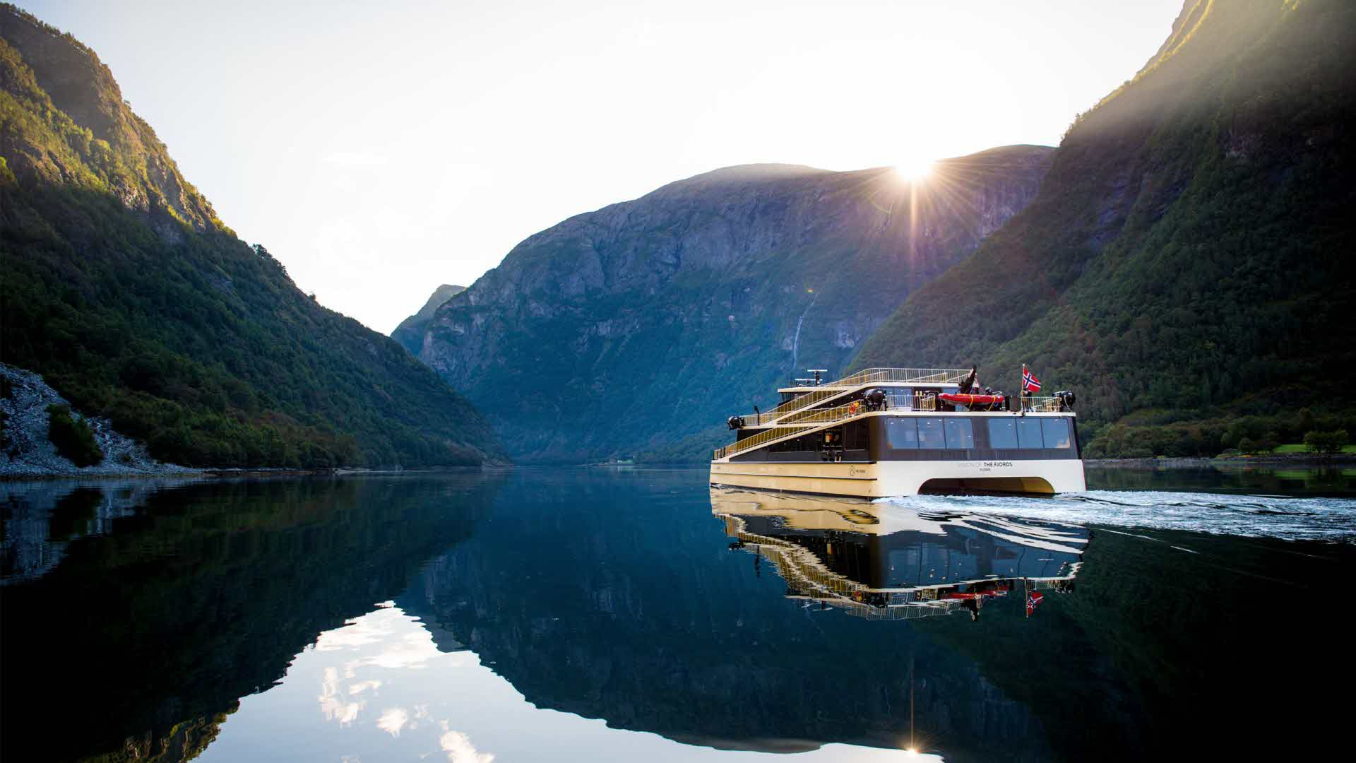 An electric boat sails across the Aurlandsfjord at dusk