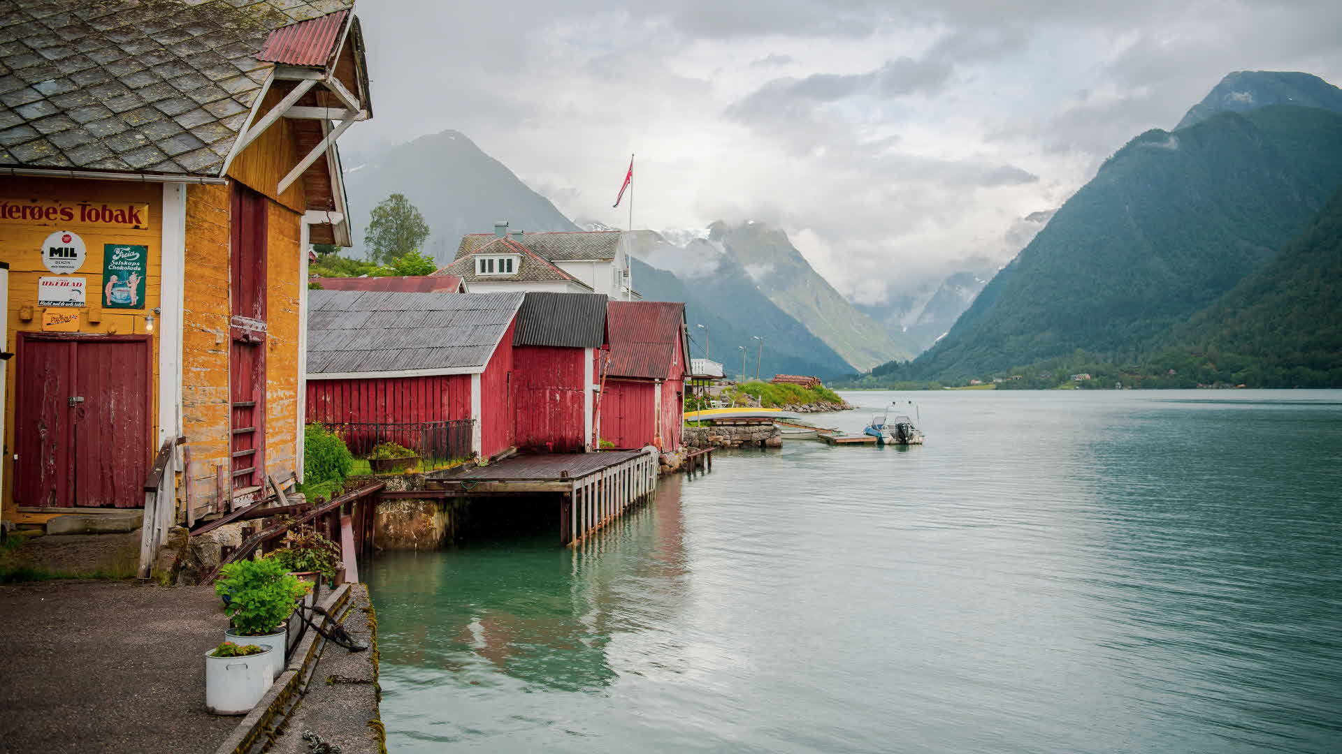 One yellow and two red boathouses along the Fjærlandsfjord, with grey clouds over the mountains