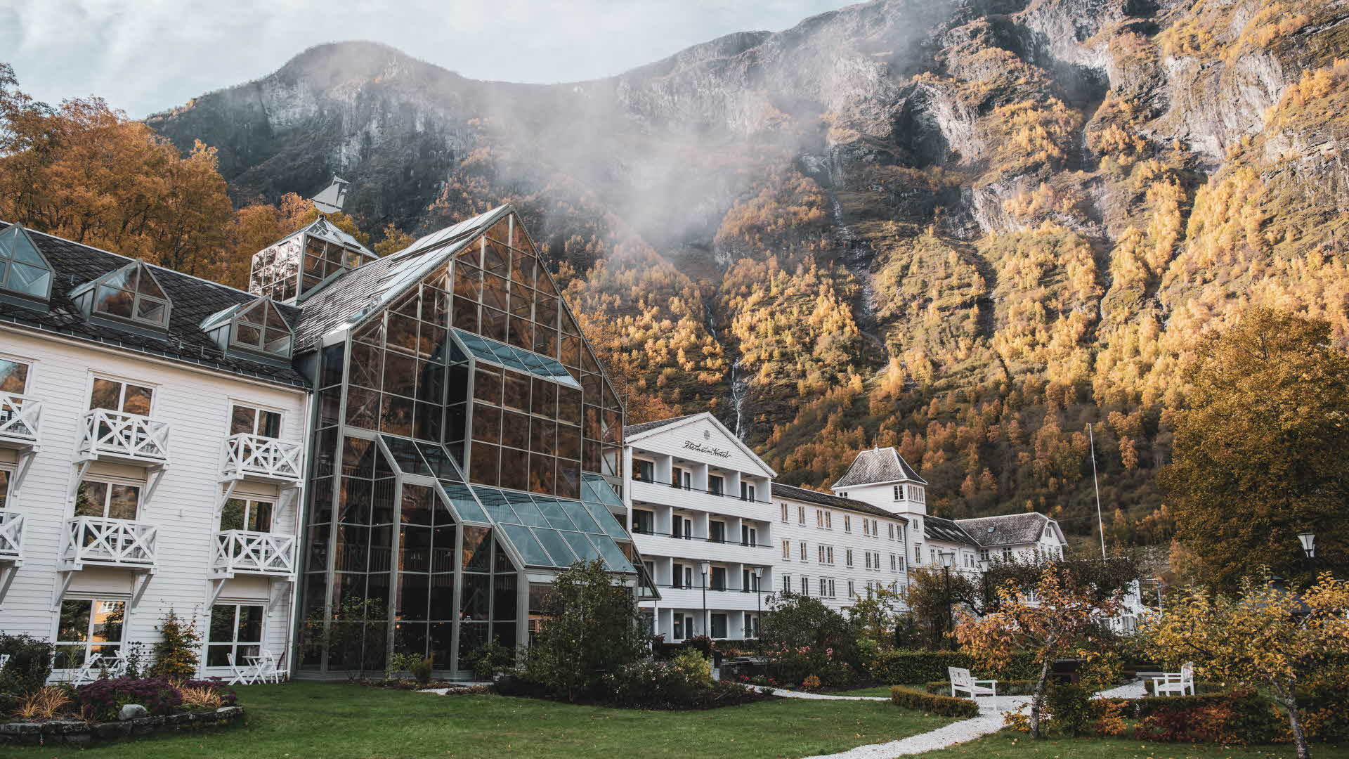 Exterior of Fretheim Hotel in autumn with the steep mountains towering behind