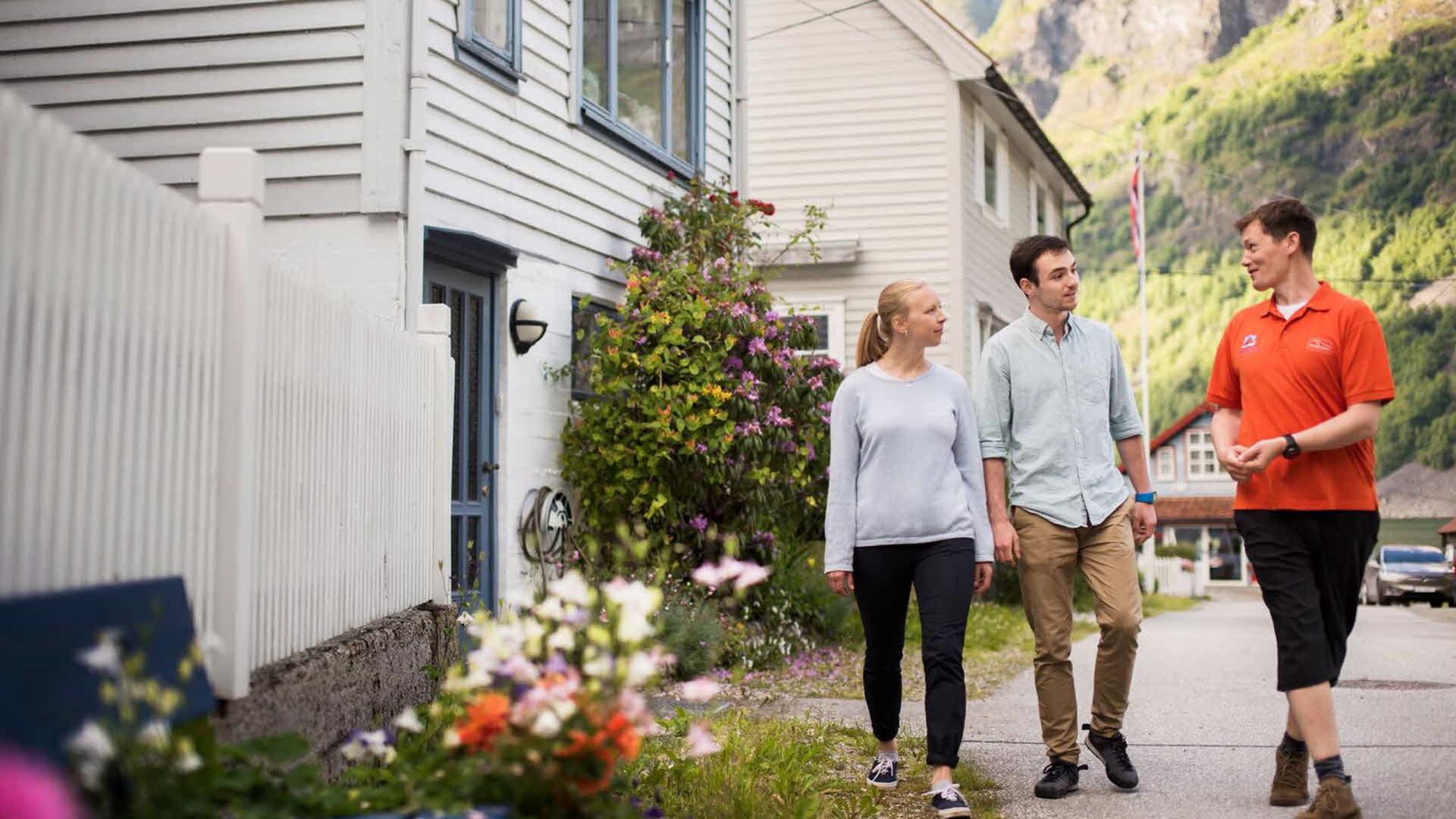 Et ungt par og en blid guide som går imellom de idylliske hvitmalte gamle husene i Undredal en vakker solskinnsdag
