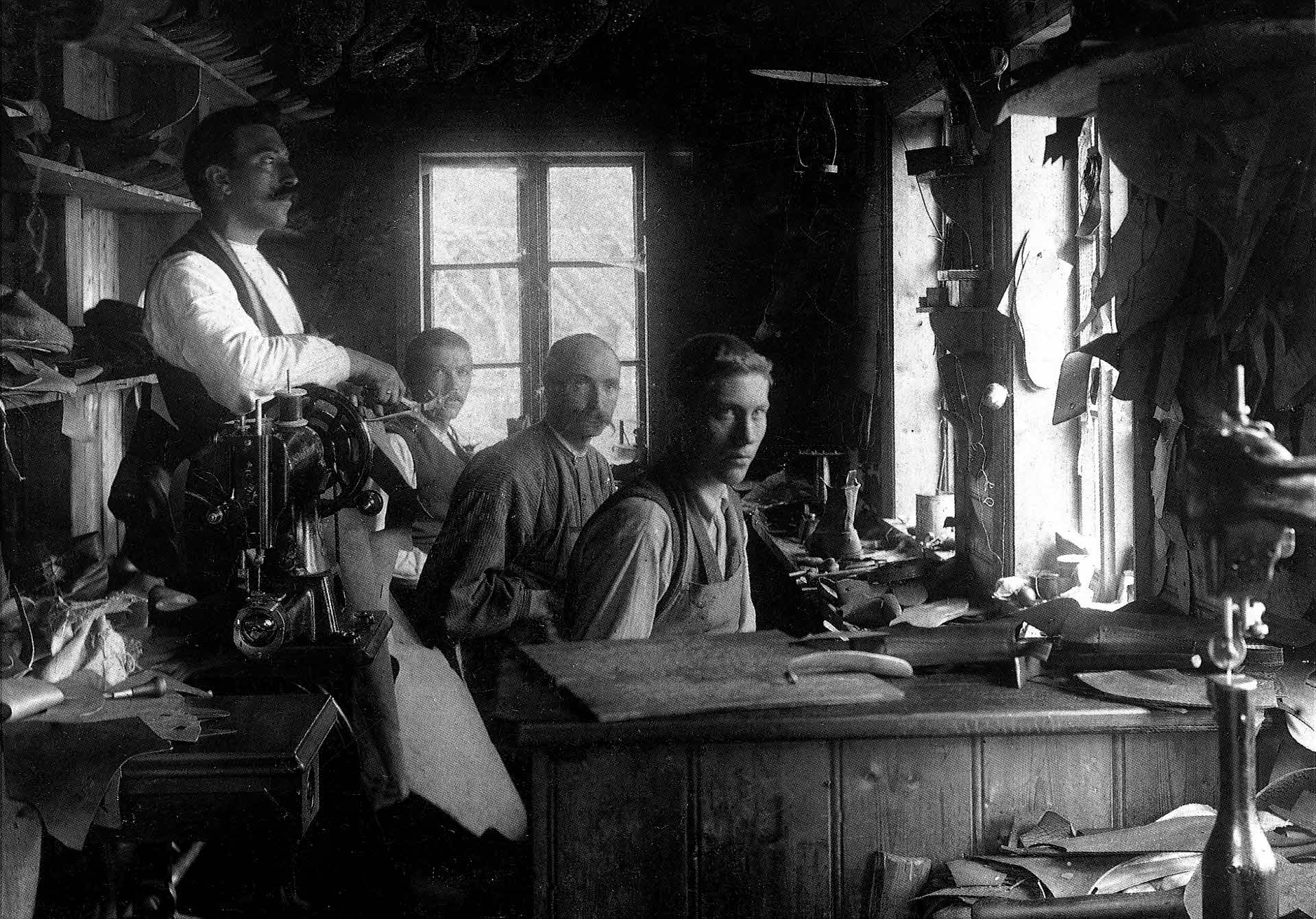 Historic photo of four men with moustache and serious faces in the 1930's sitting and working in the Aurland Shoe Factory.