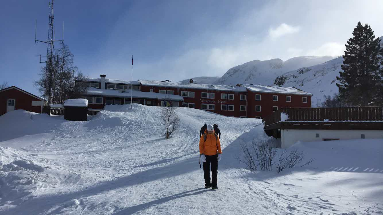 Vatnahalsen Hotel seen from a distance packed in snow, woman in orange winter jacket walks towards camera