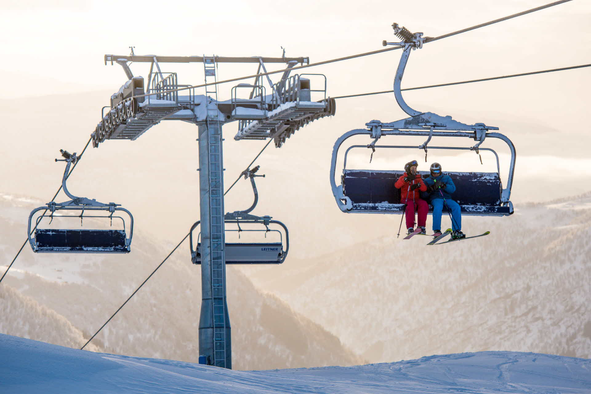 2 people in alpine downhill gear sitting in ski lift in Myrkdalen Ski Resort surrounded by snowy mountains