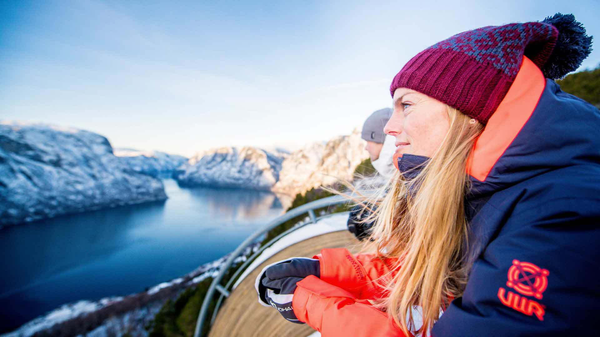 A woman and a man leaning on Stegastein viewpoint looking at the Aurlandsfjord and snow-covered mountains