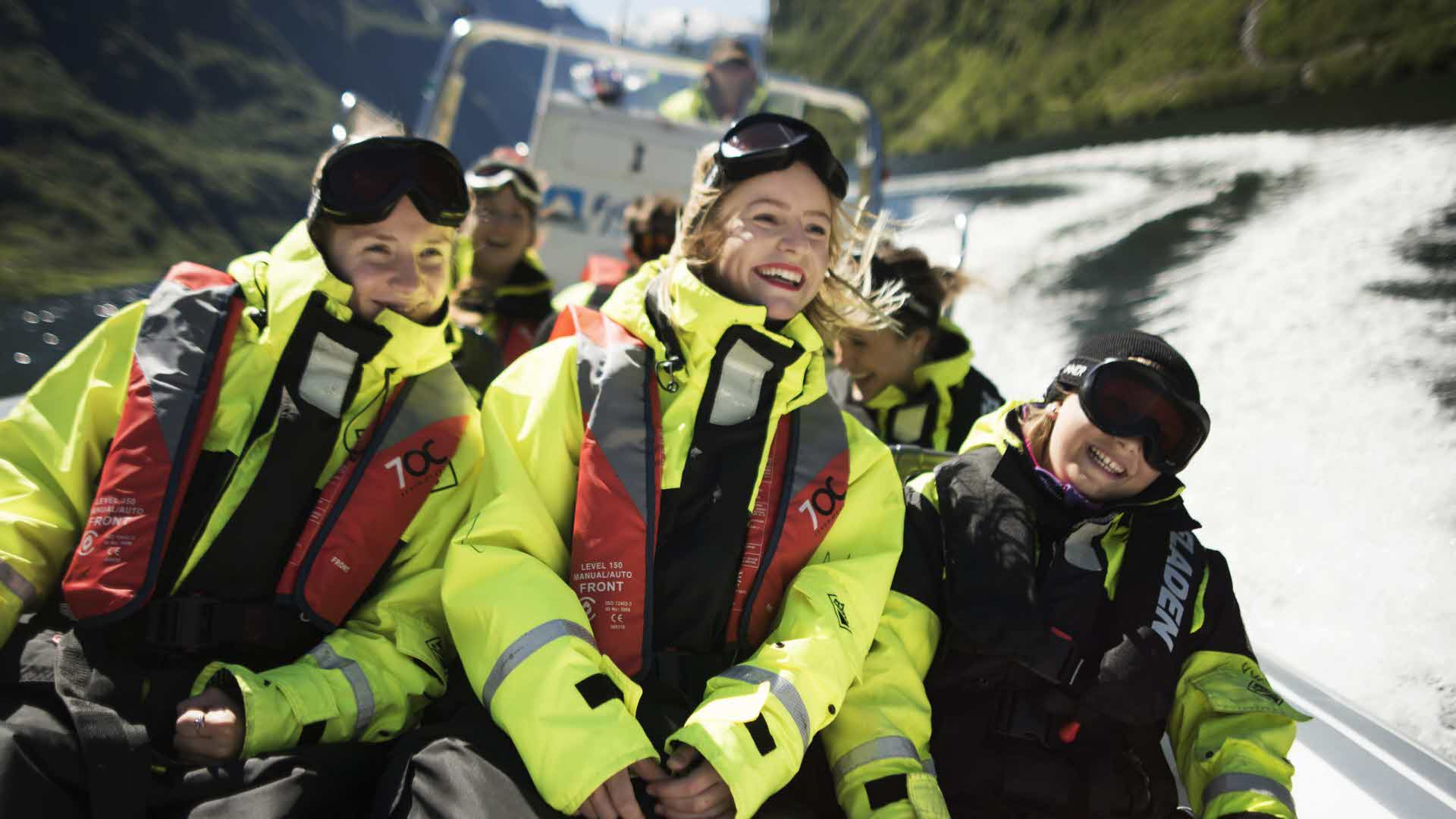 3 smiling people sitting in their life suits on rib boat full speed through Naroyfjord