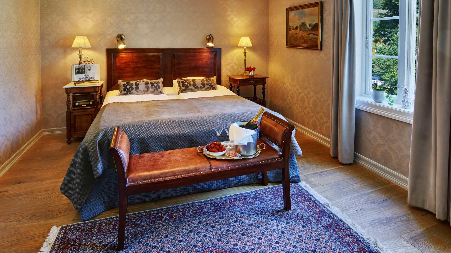 Historisk rom på Fretheim Hotel med dobbeltseng, vindu med utsikt mot hagen og et brett med champagne, glass og jordbær stående på en antikk sittebenk i skinn.