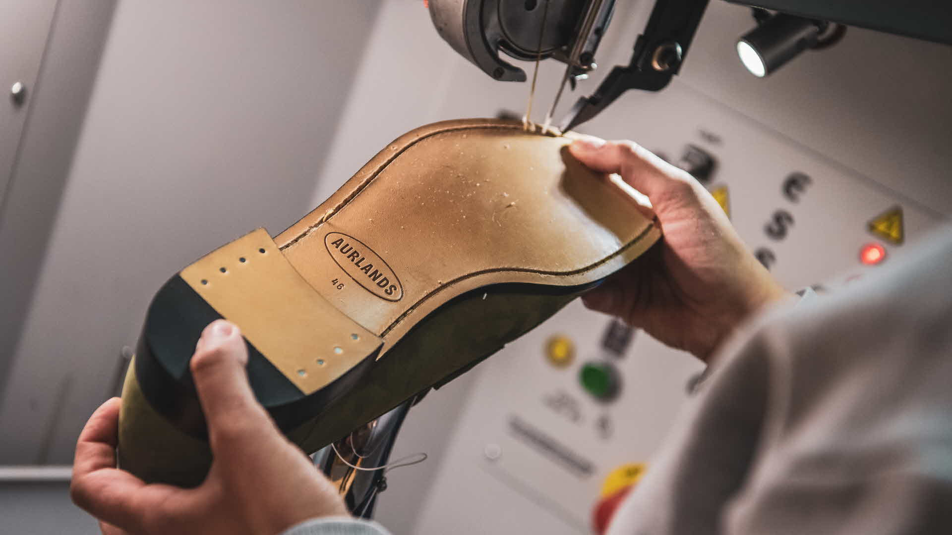 Worker is stitching underside sole of Aurland shoe. Aurlands new logo is popping in the mini spotlight attached to sewing machine.