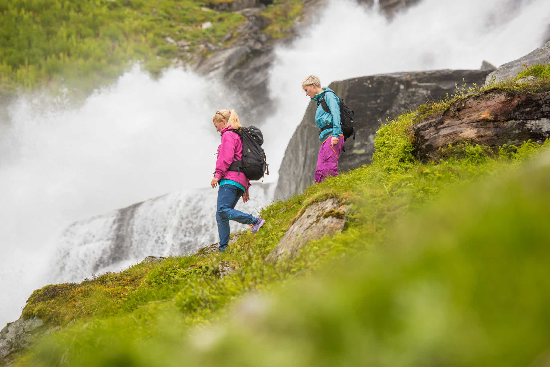 Two women walking down along a waterfall at Vikafjell