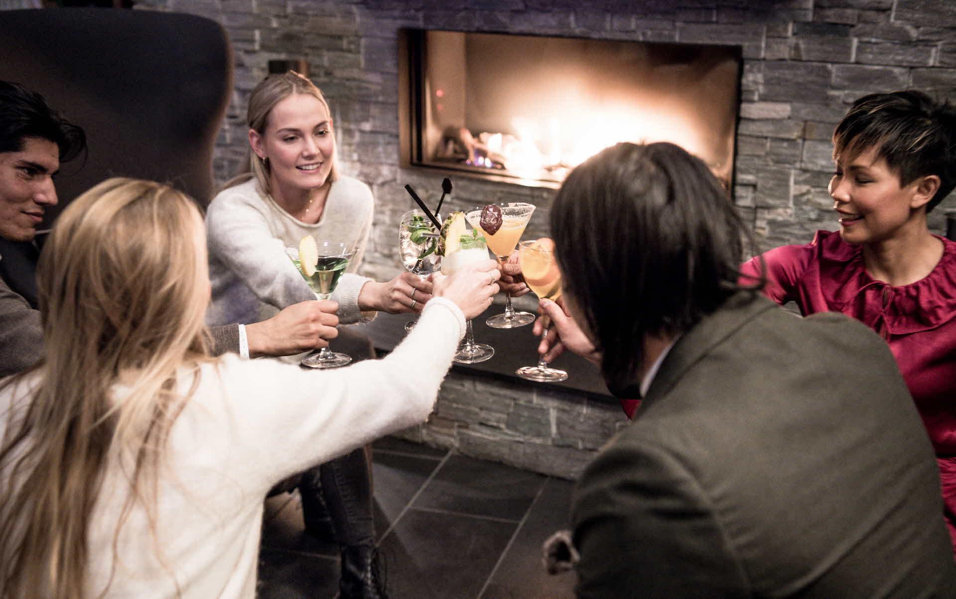 To menn og tre kvinner skåler smilende med drinken i Salto Lobbybar