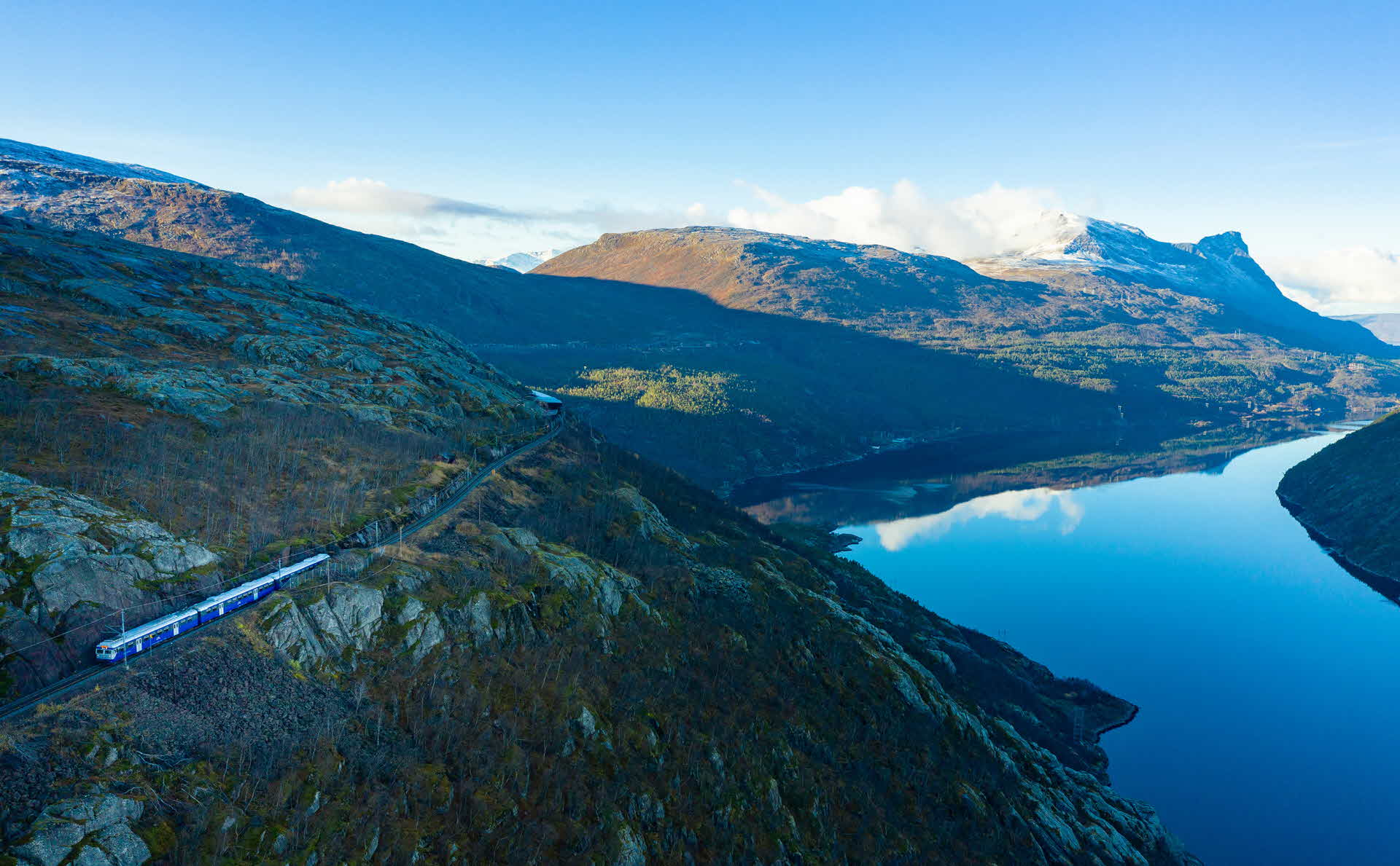 The blue 3 coach Acrtic Train snails up the mountain in autumn by the still Rombaksfjord far below in Narvik Norway