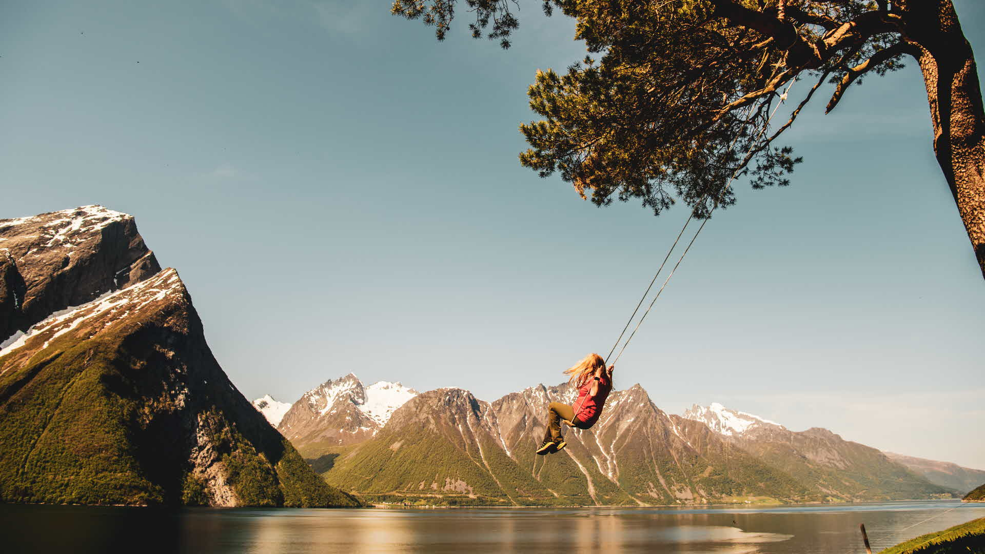 Woman enjoying tree-swing at Trandal farm by Hjorundfjord. Dramatic alpine mountains with snow-capped mountains