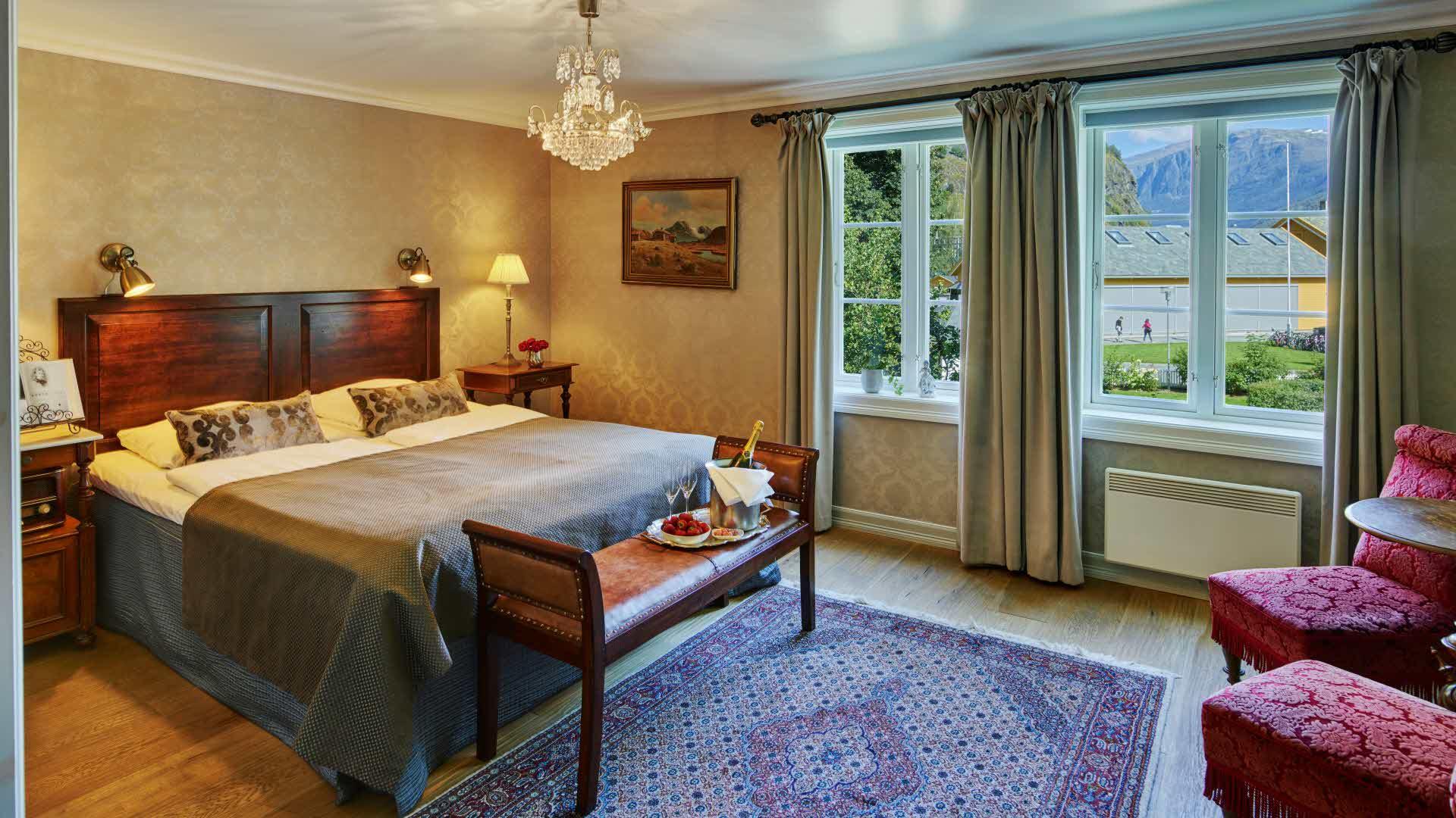 Et historisk rom på Fretheim Hotel med dobbeltseng, to røde antikke loungestoler, lysekrone og utsikt mot Flåm