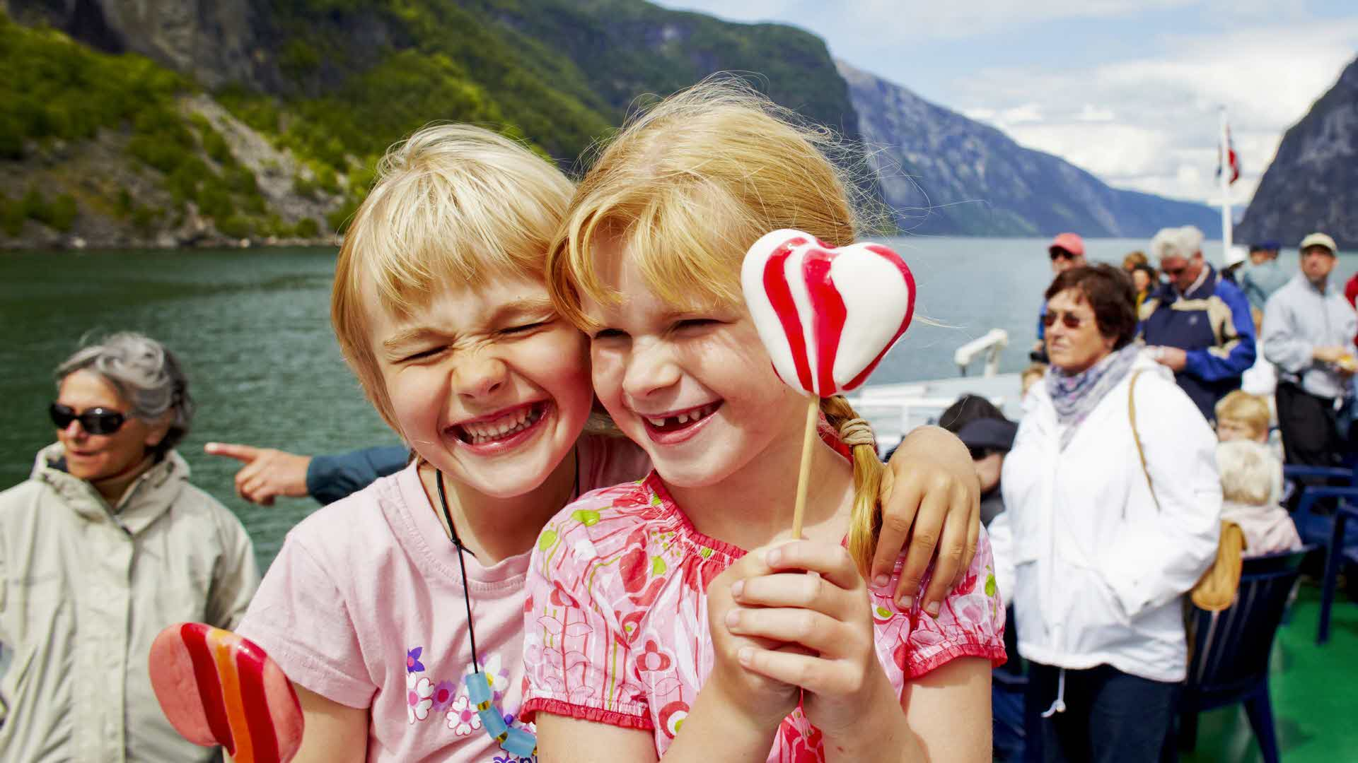 Two happy girls enjoying their lollypops on board classic vessel sailing through Naeroyfjord