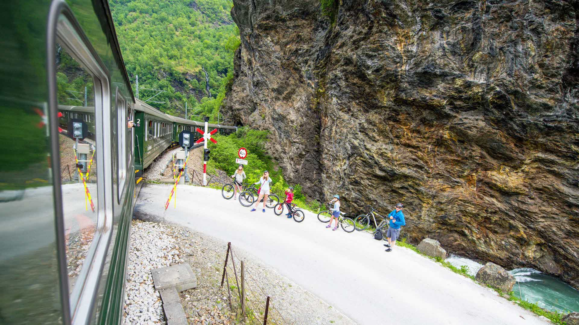 Family of 5 stops and wait on their bikes on gravel road in the Flam valley as The Flam Railway passes in summer