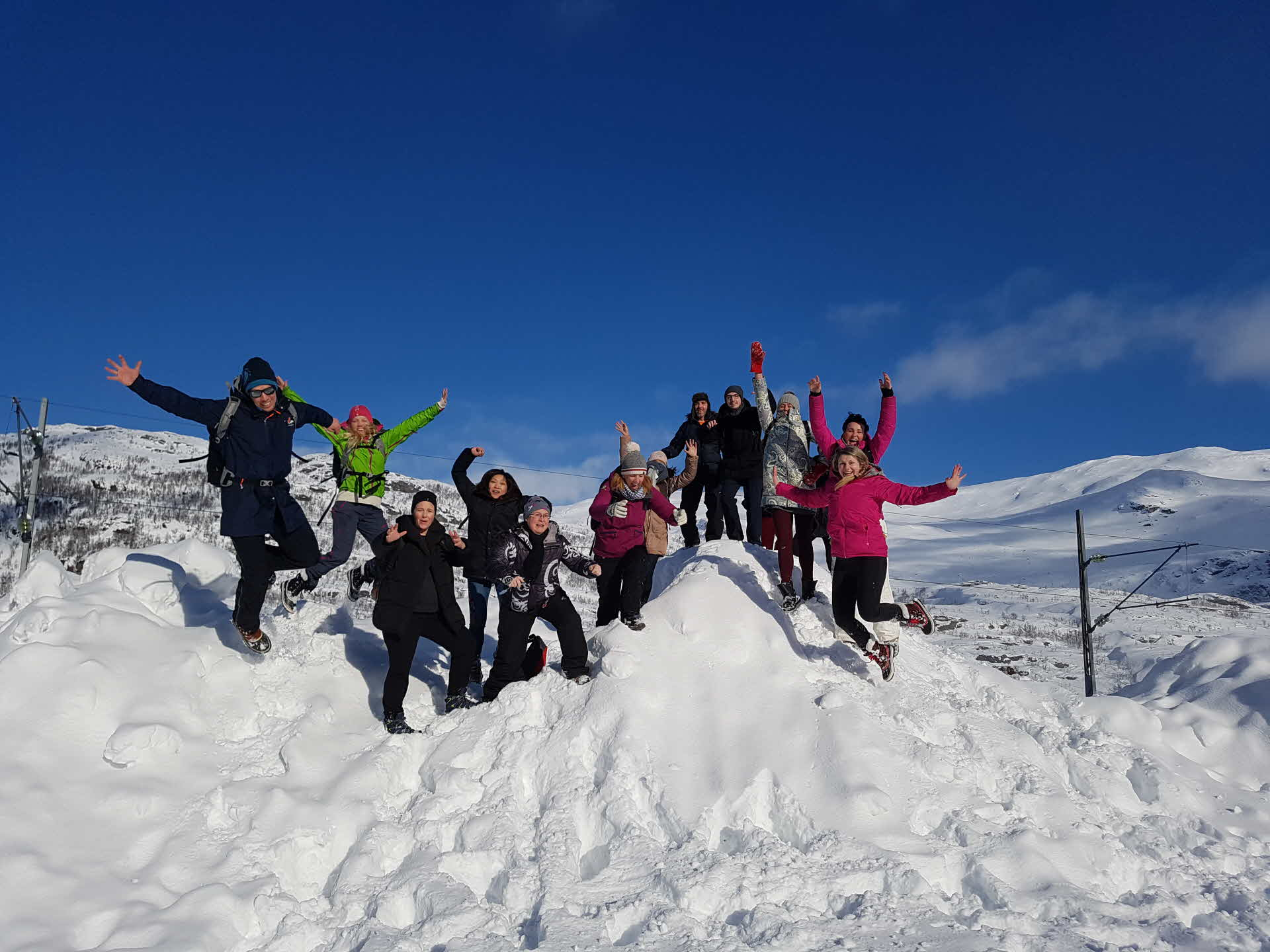 Group of people in winter clothing jumping up in the air and smiling on top snow hill in sunshine, blue skies.