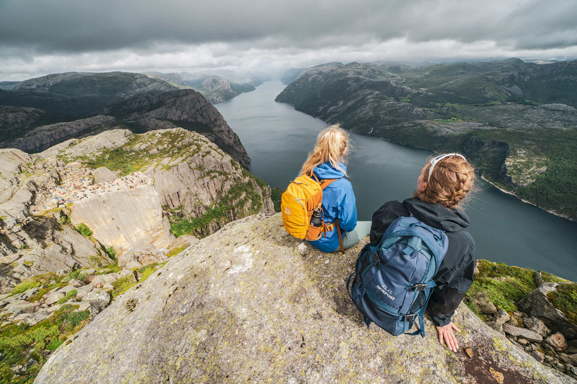 2 women in hiking gear sitting on top of mountain overlooking Lysefjord below on a cloudy day