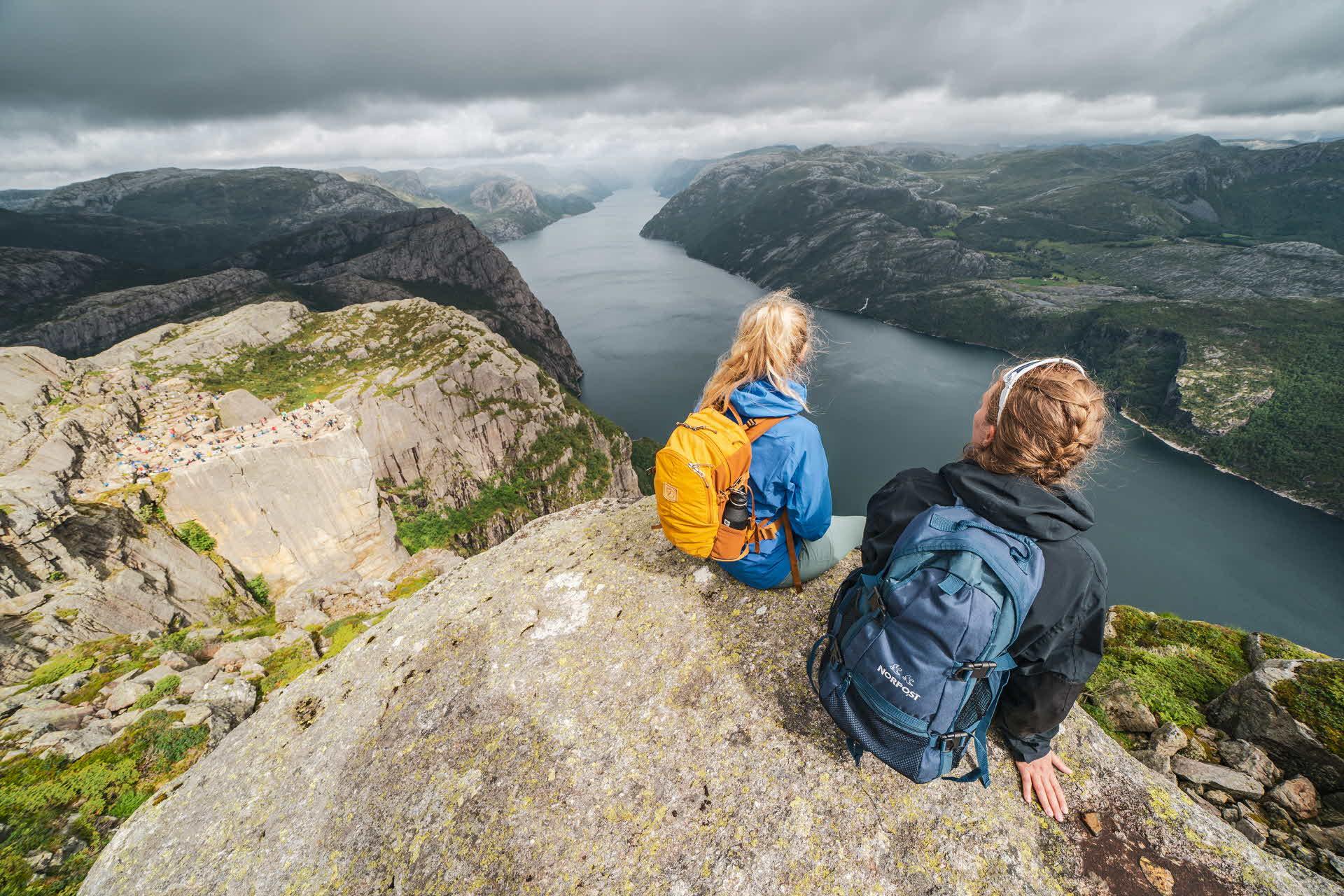 2 kvinner i fjellbekledning sitter på en fjelltopp og ser utover Lysefjorden på en rolig skyet sommer dag