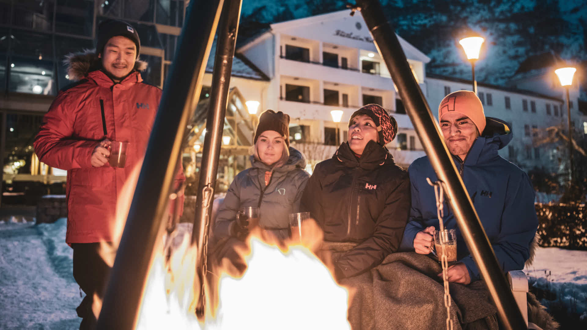 Four people drinking hot drinks around bonfire in front of Fretheim Hotel.
