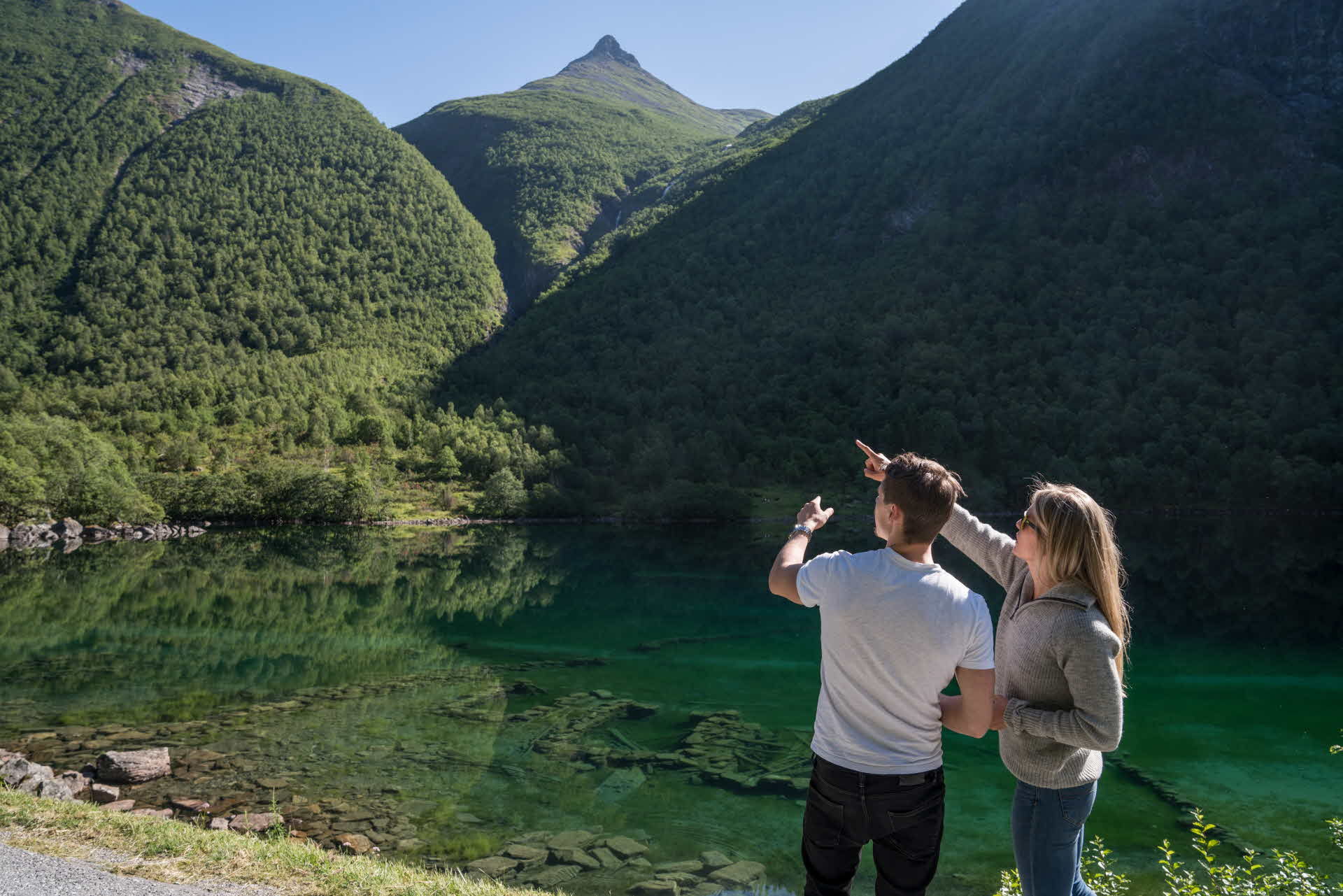 A woman and a man standing next to the ruins of the farm under the water in Norangdalen