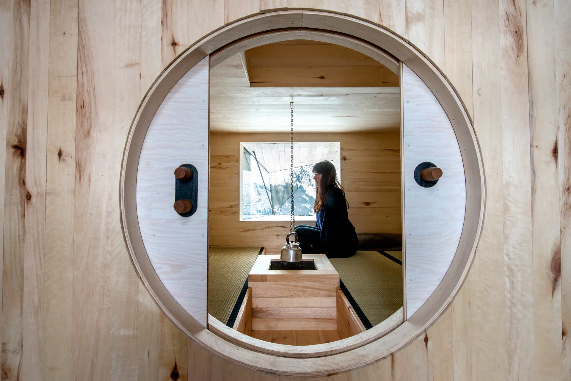 A woman looking through a round window while sitting on a bed