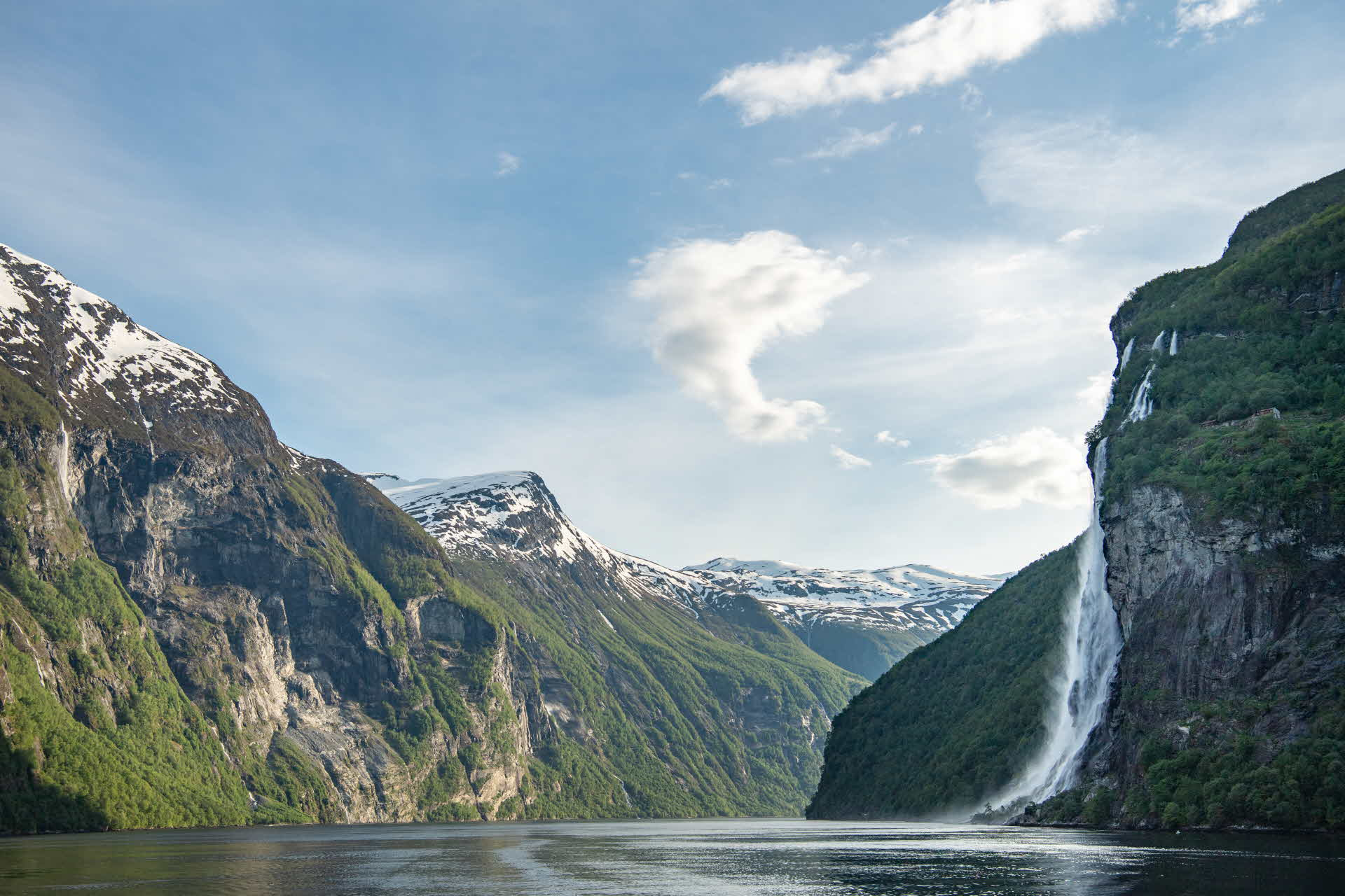 A spring day at the Geirangerfjord, with snow on the mountains and a large waterfall