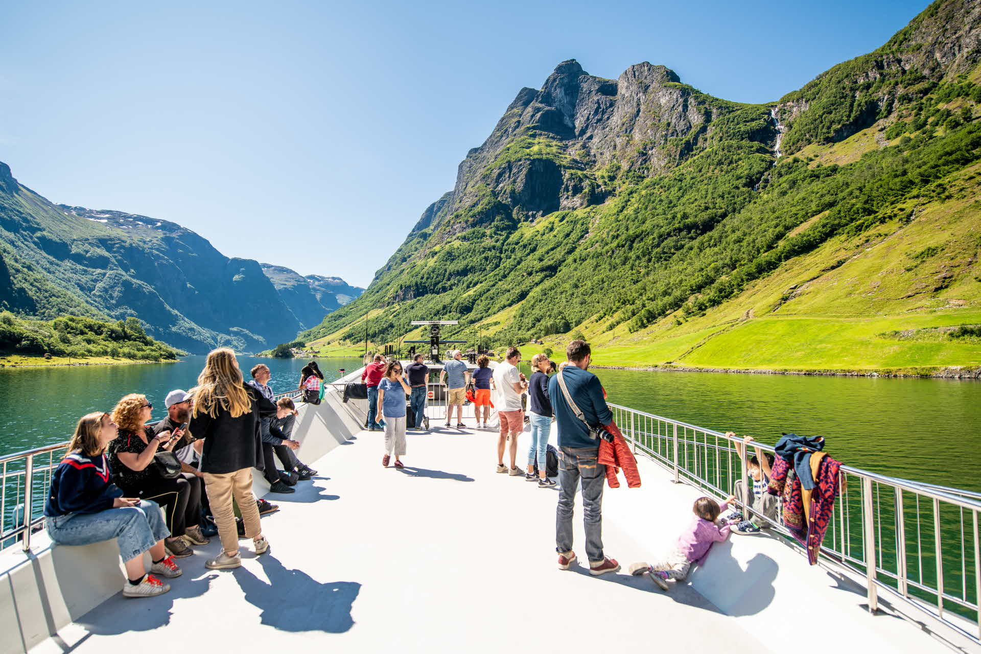 Panorama view of Naeroyfjord on top deck of Future of The Fjords as group of tourists are enjoying the dramatic scenery