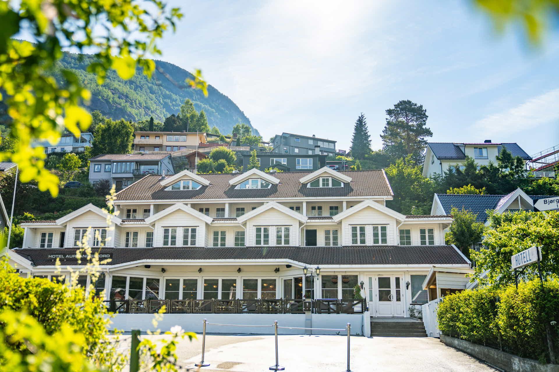 Hotel Aurlandsfjord sett fra vegen med terrasse og parkering foran