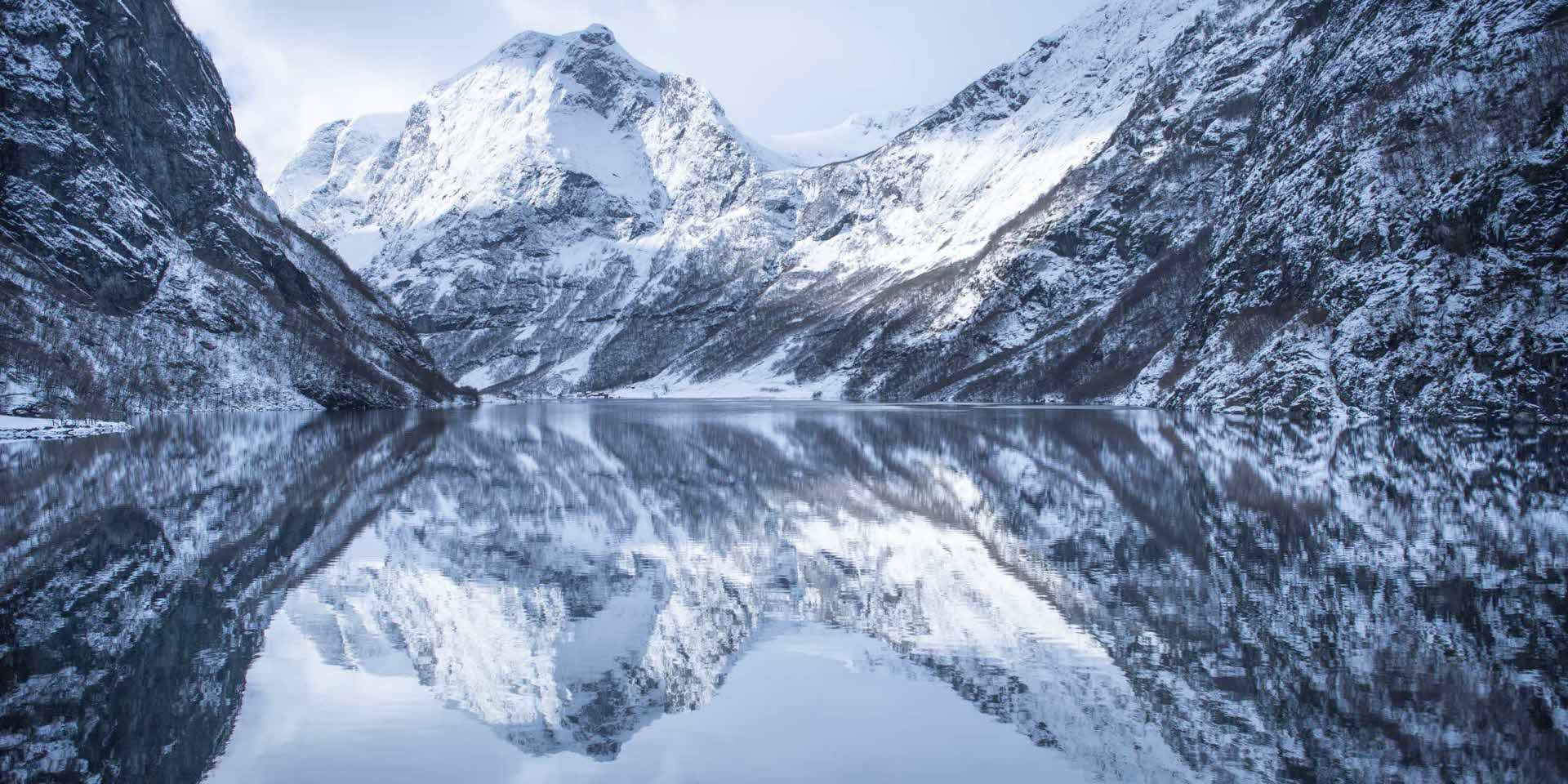 Nærøyfjord in winter with snow clad peaks and still fjord