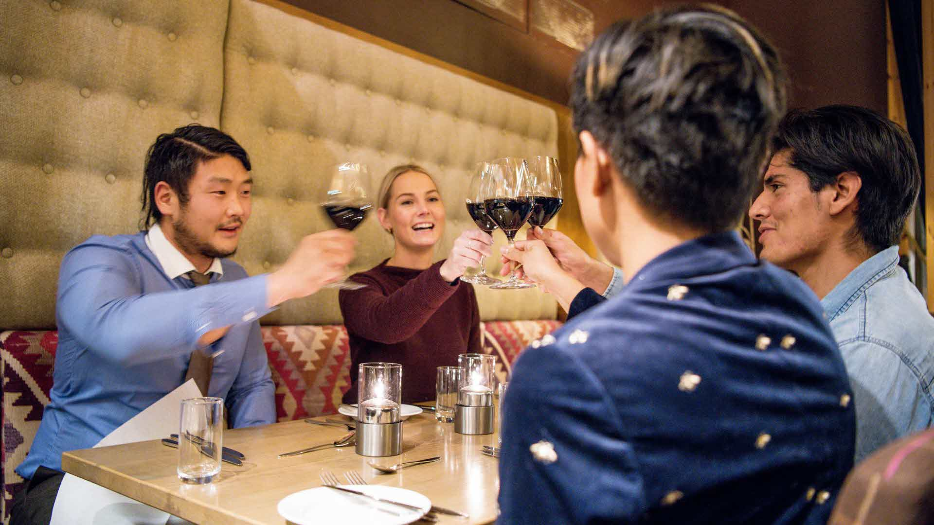 Four people toasting and smiling around a table at Restaurant Arven