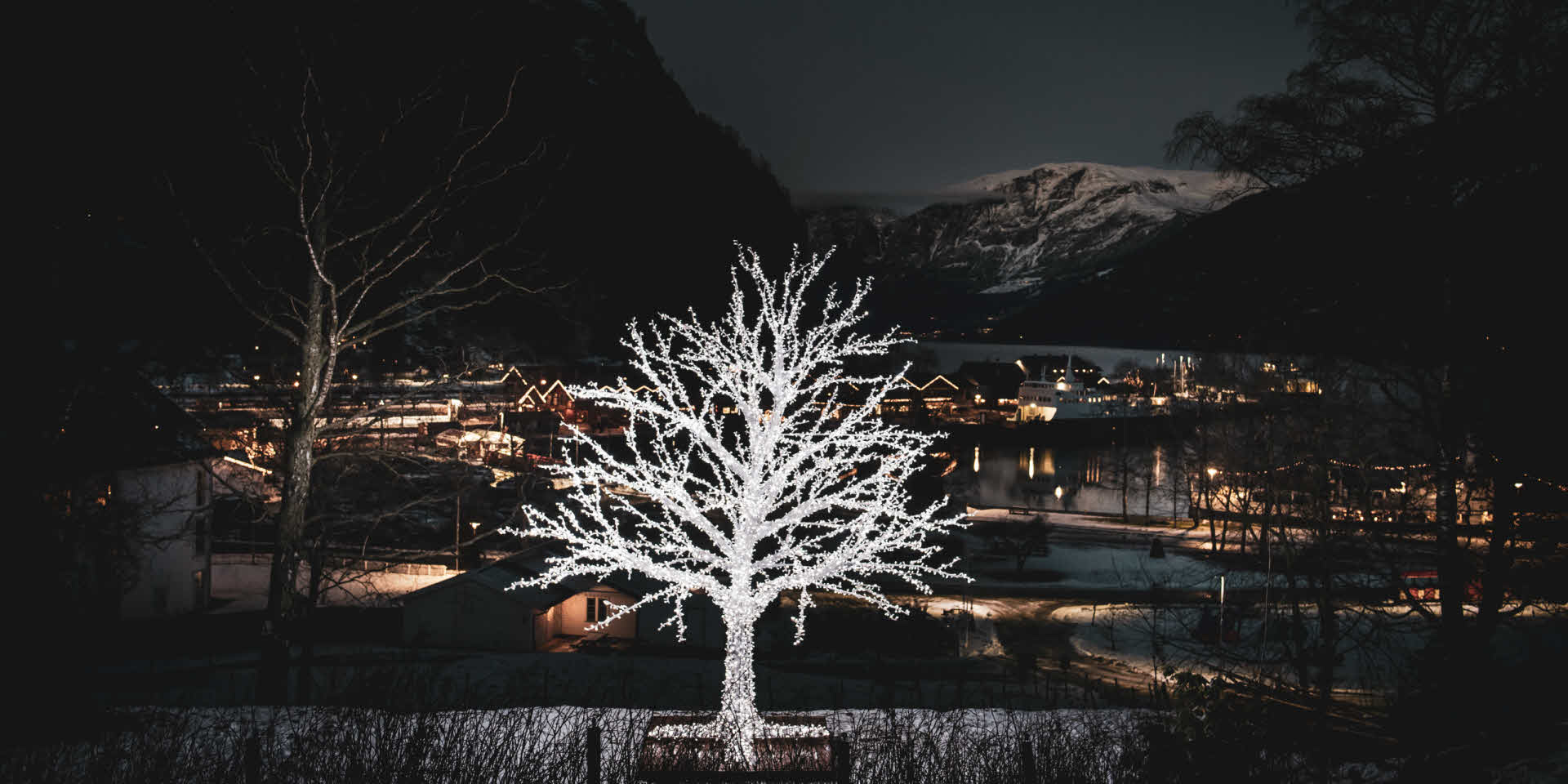 A decorative light tree in front with Flåm and snowy mountain peak in the background