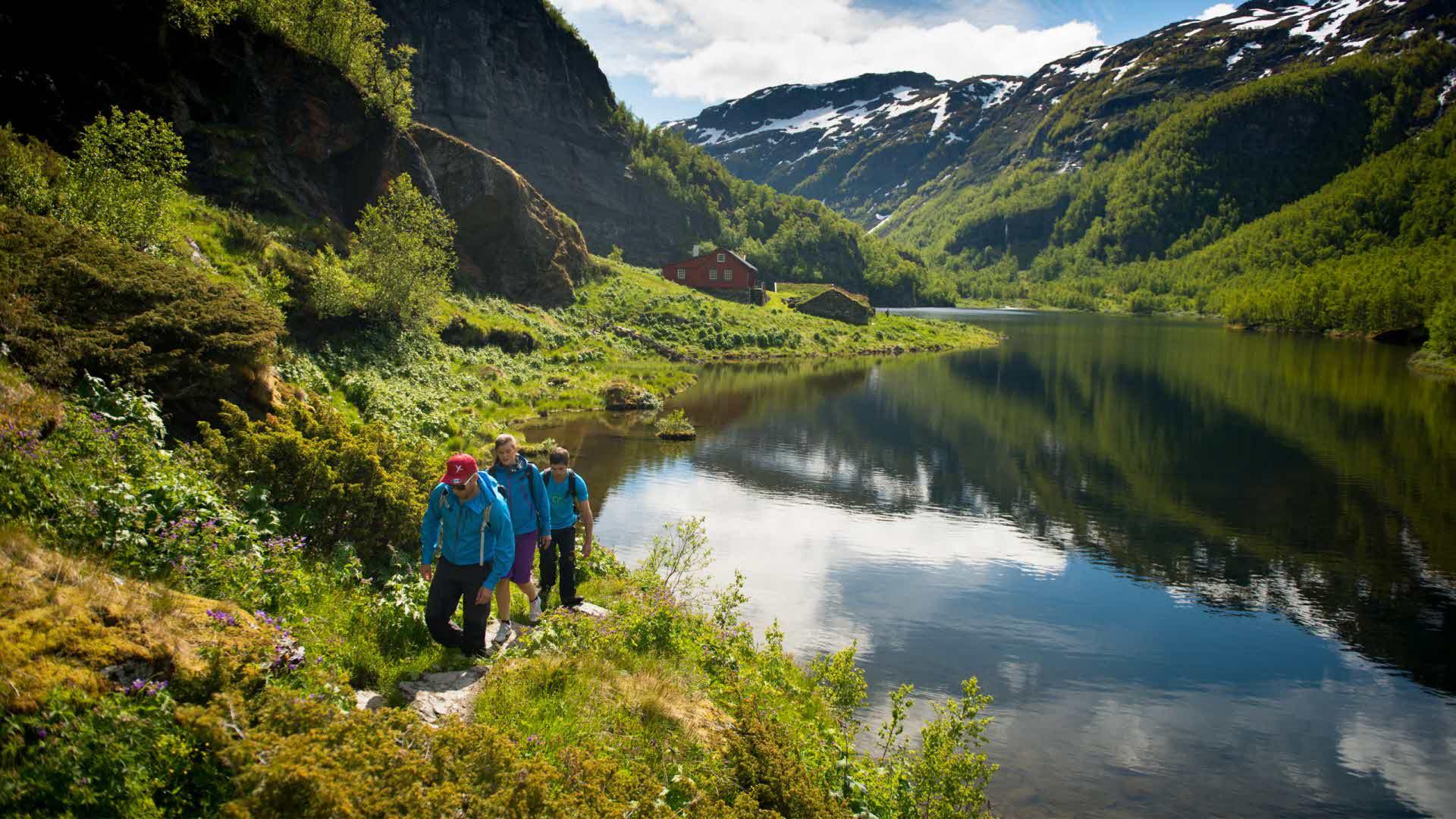 3 turgåere går langs stille vann i vakre og dramatiske Aurlandsdalen om sommeren