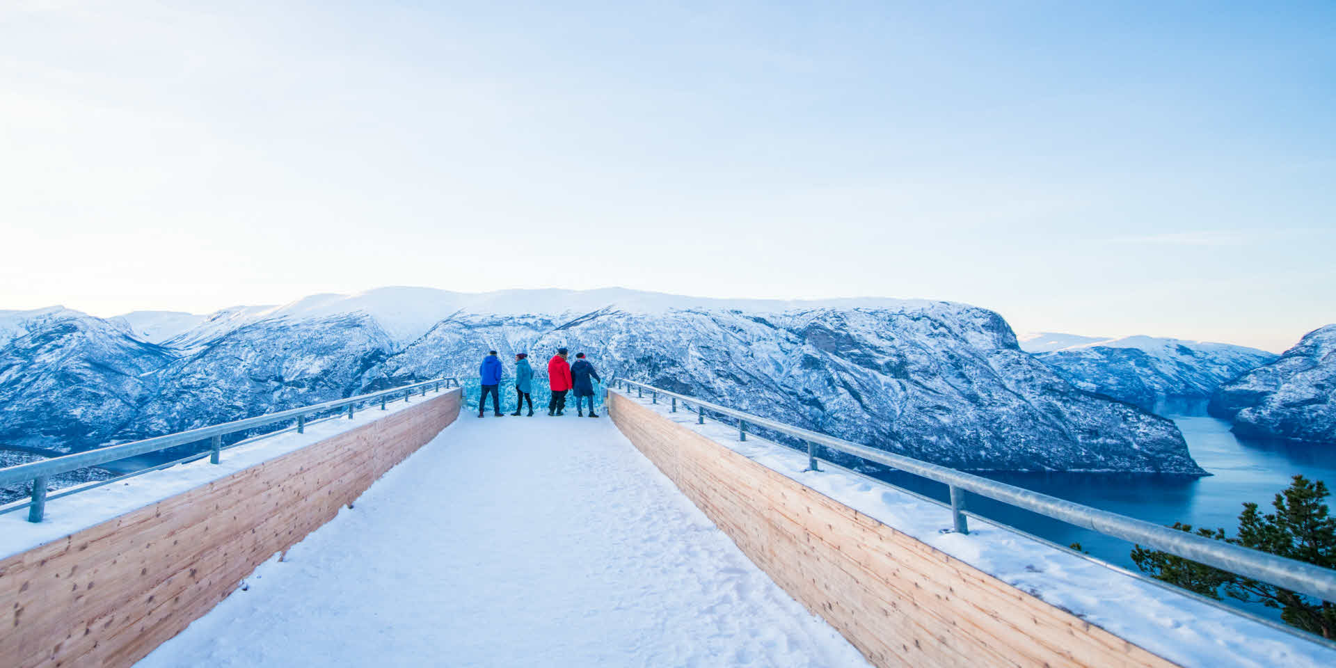 Stegastein in winter. Four people looking over Aurlandsfjord and winter landscape