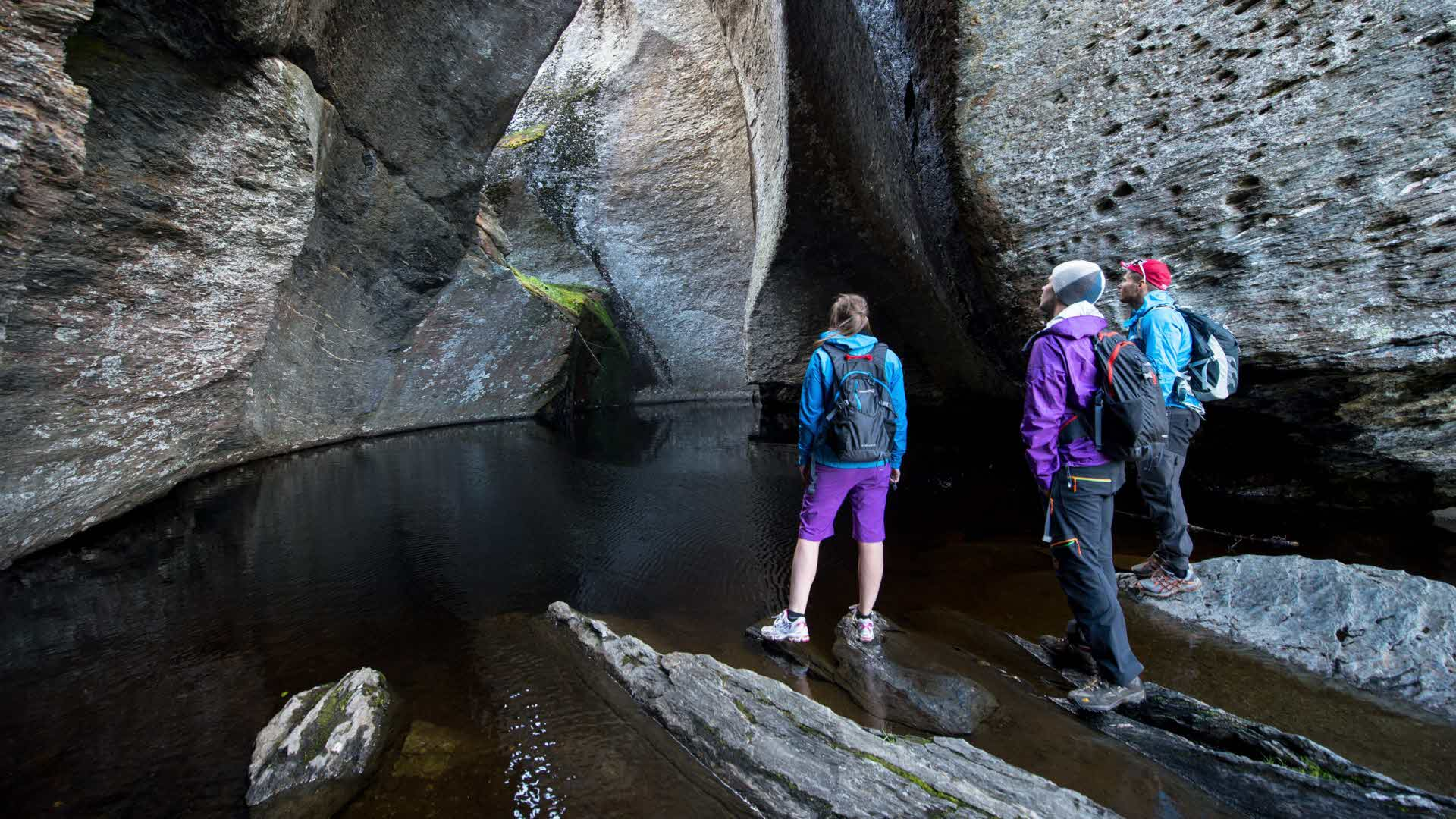 3 hikers standing beside the waterfront of an open-air cave in Aurland Valley in autumn called Vetla Helvete (Little Hell)
