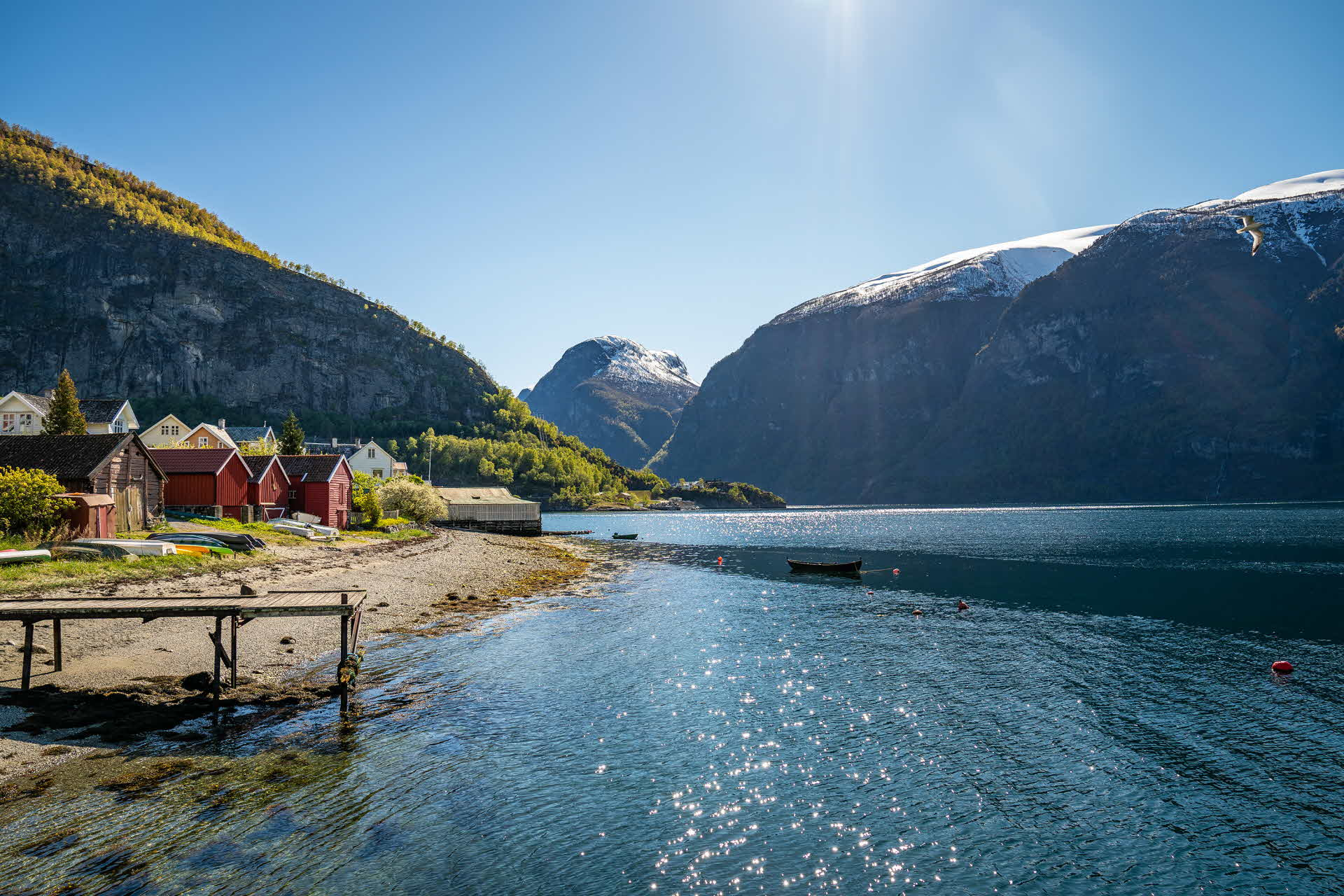 Boat houses at the shoreline by the UNESCO listed Aurlandsfjord in summer. Lush mountain sides with snow-capped mountains