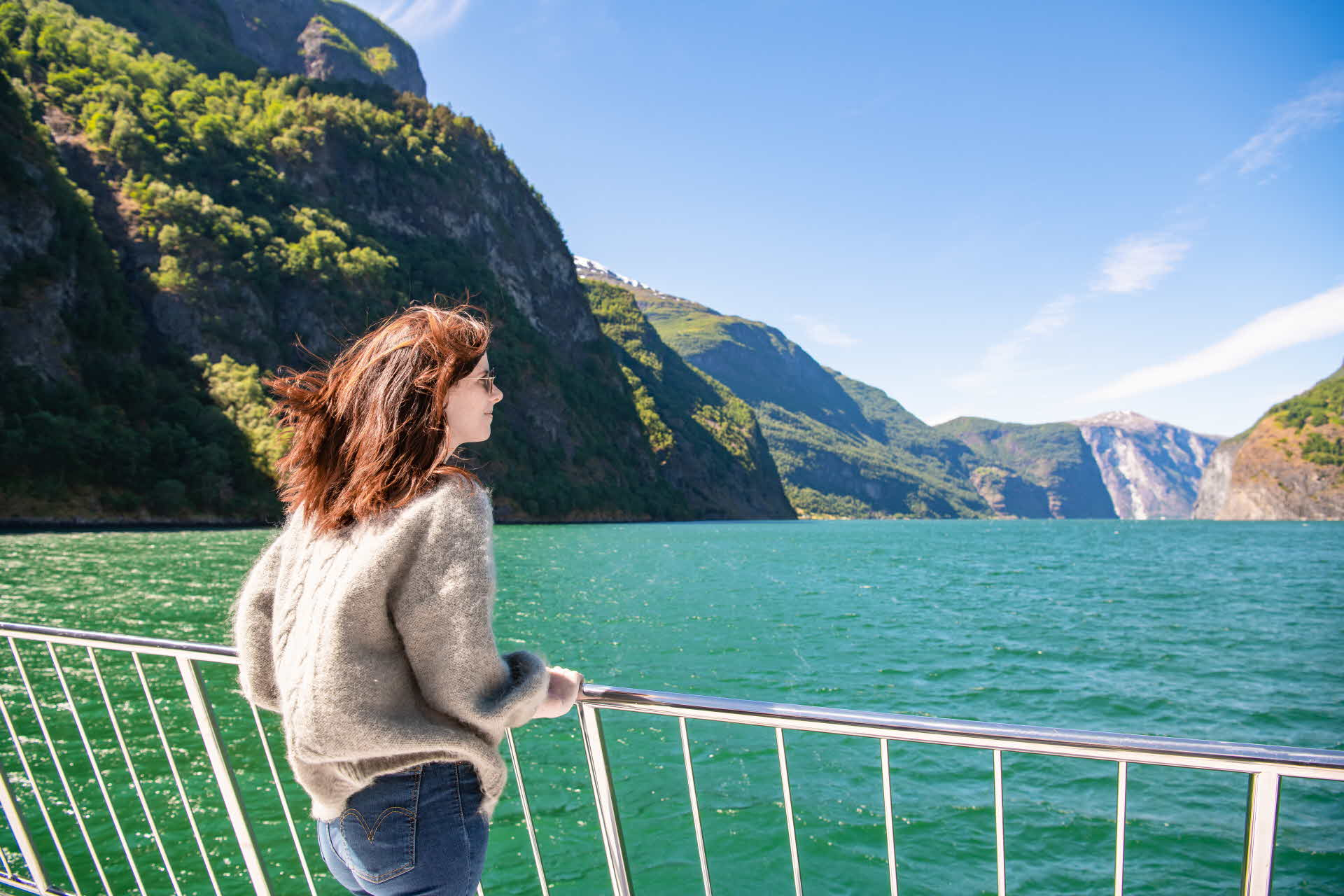 A woman standing on the bow of an electric boat and looking out over the fjord