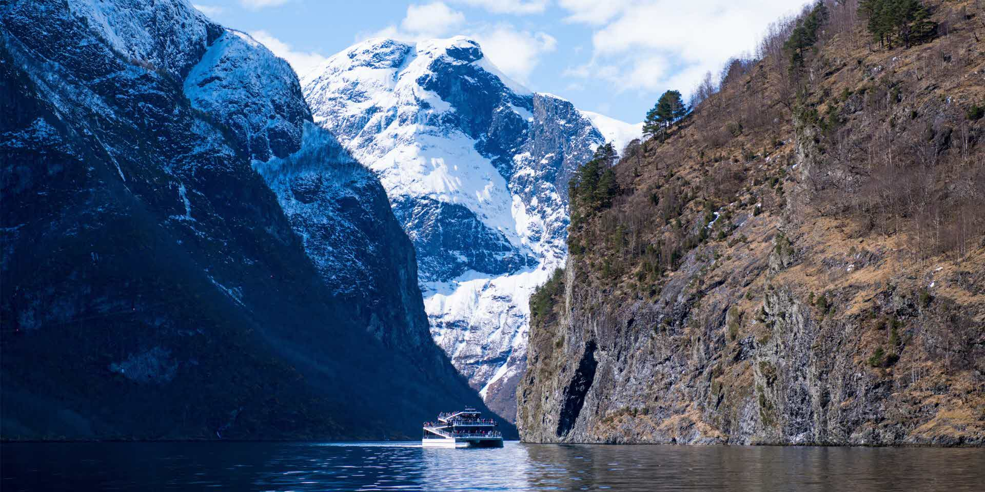 Future of The Fjords sailing on the Nærøyfjord in late winter with snow capped mountain behing and people standing on deck