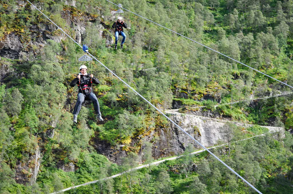 2 happy people travelling side-by-side down the Flåmsdalen Valley on the Flåm Zipline