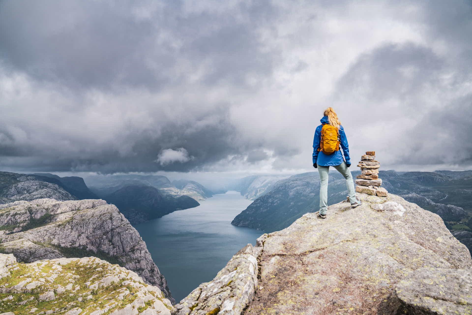 Kvinne i fjellbekledning står på toppen av et fjell med utsikt over Lysefjorden på en overskyet dag
