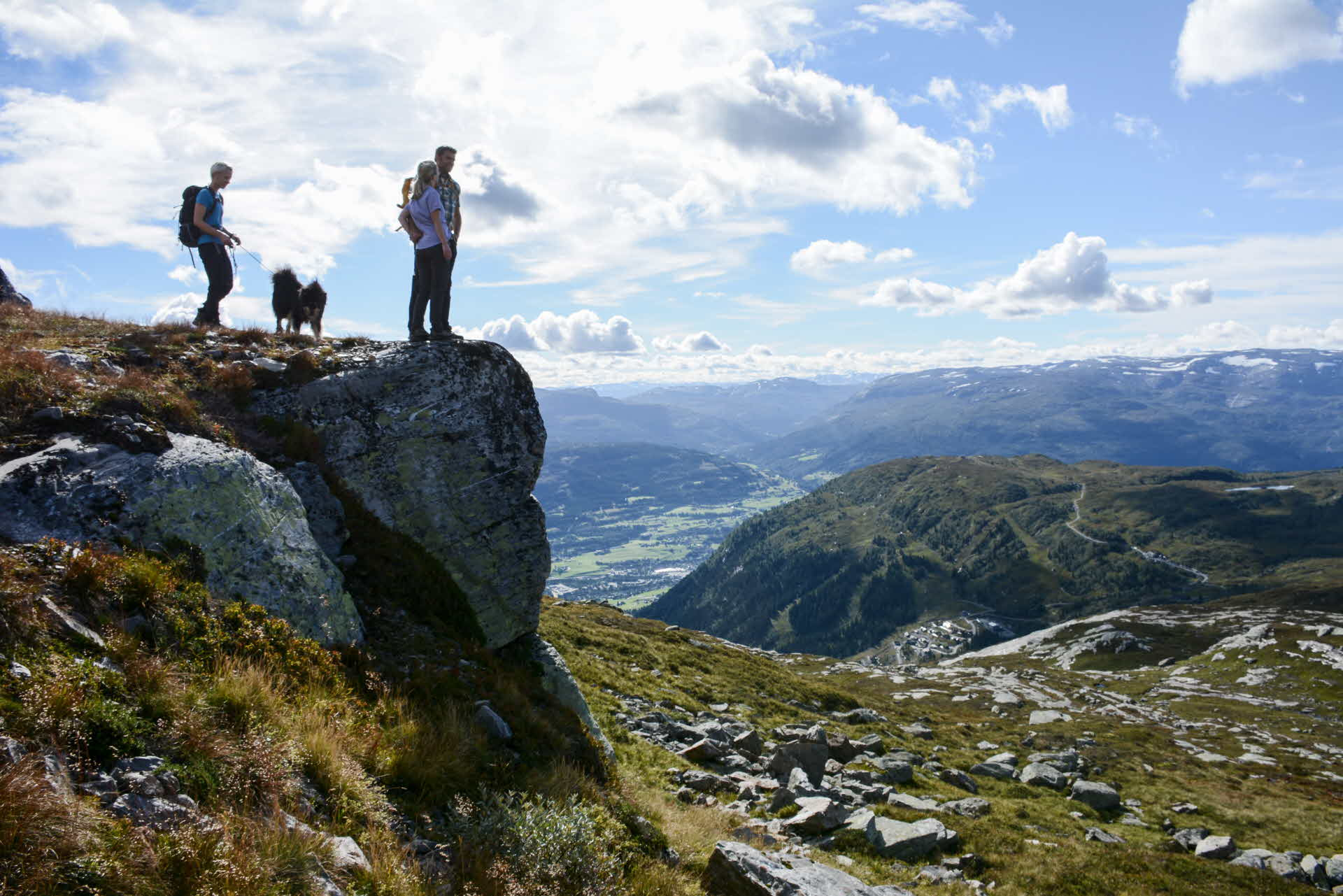 Woman with dog and couple in hiking gear overlooking the amazing view from Hangurtoppen mountain above Voss in summertime
