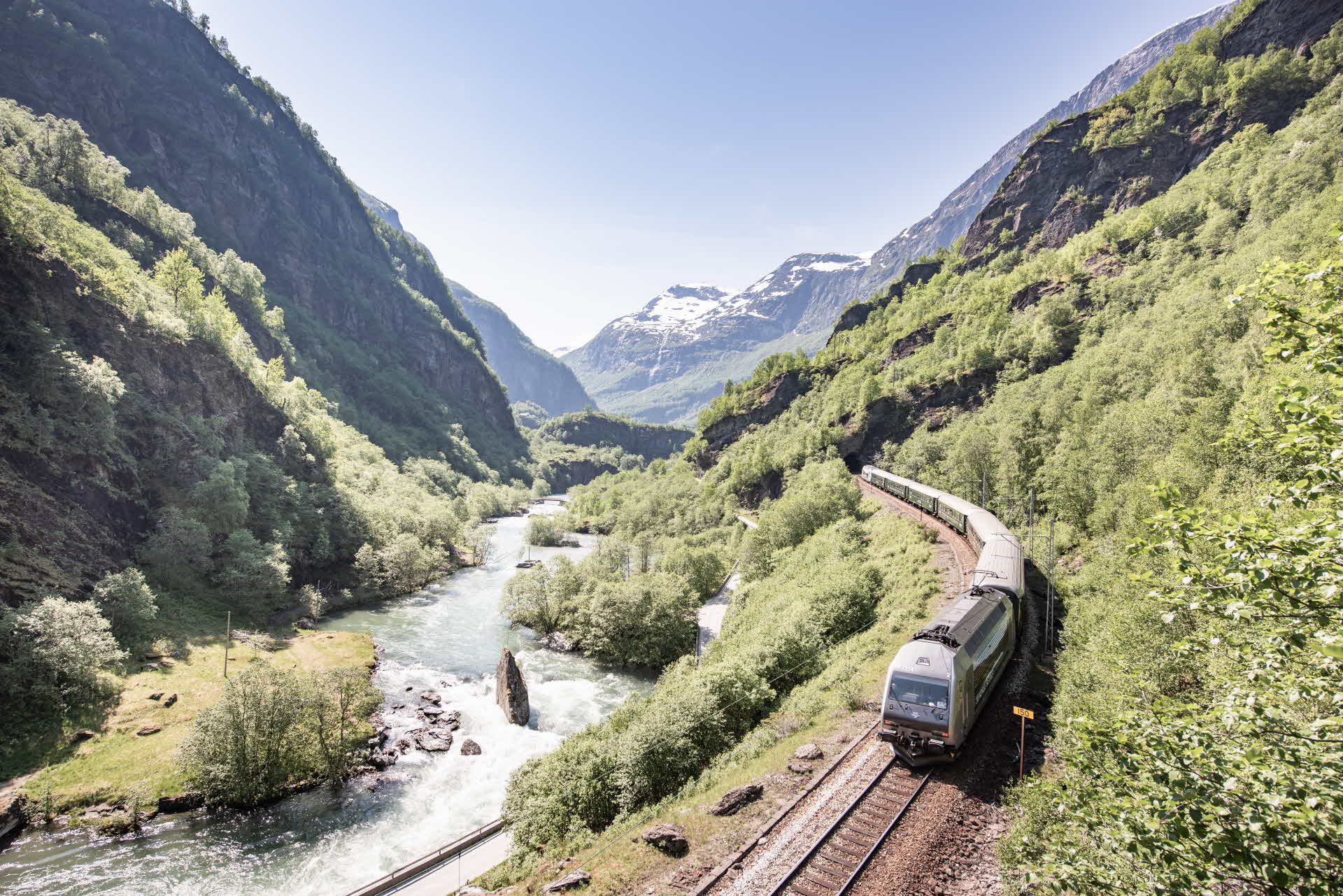 The Flåm Railway travels past a green valley next to the river