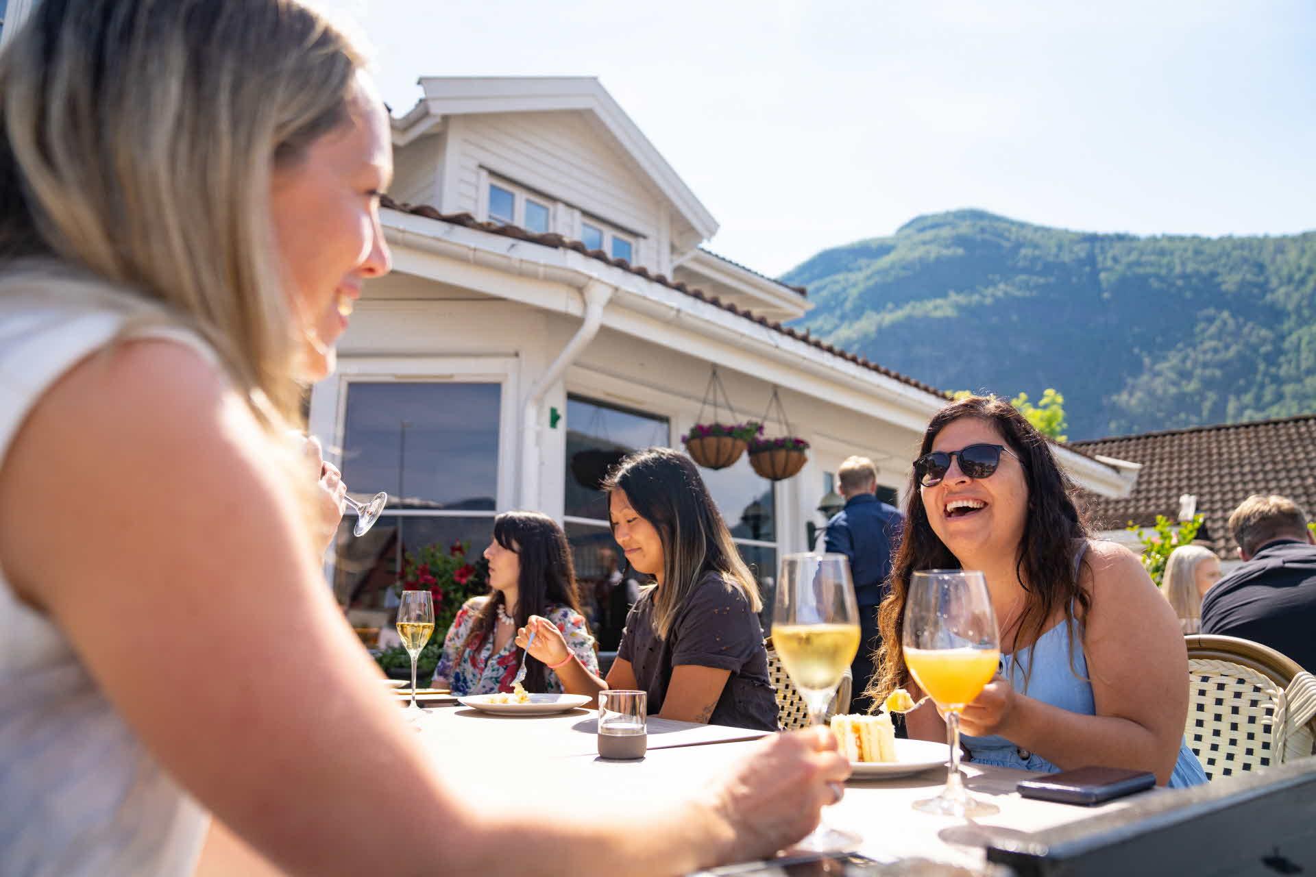 To kvinner ler mens de spiser kake på terrassen utenfor Hotel Aurlandsfjord