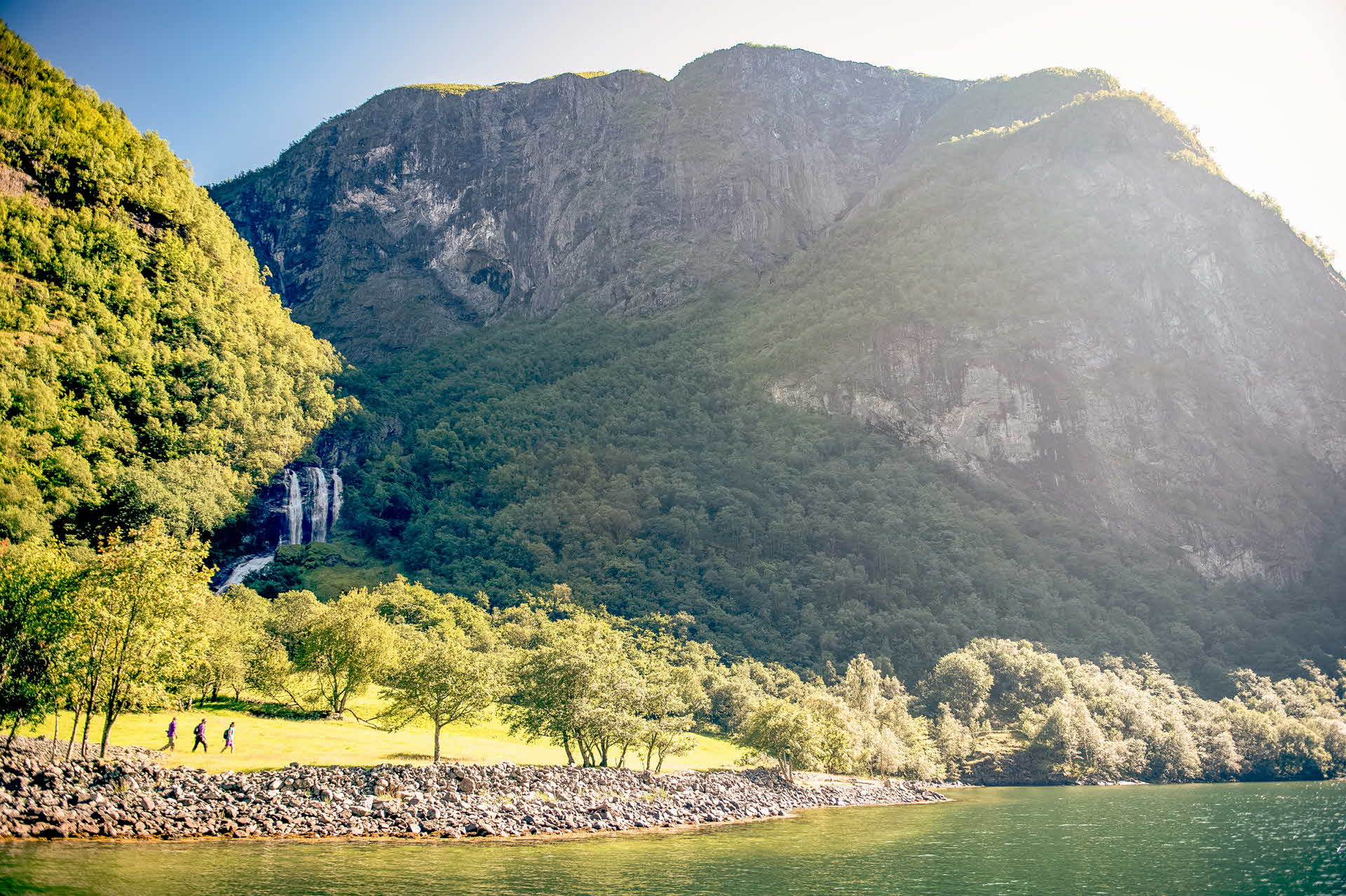 Drei Personen wandern entlang des Nærøyfjords über eine grüne Wiese