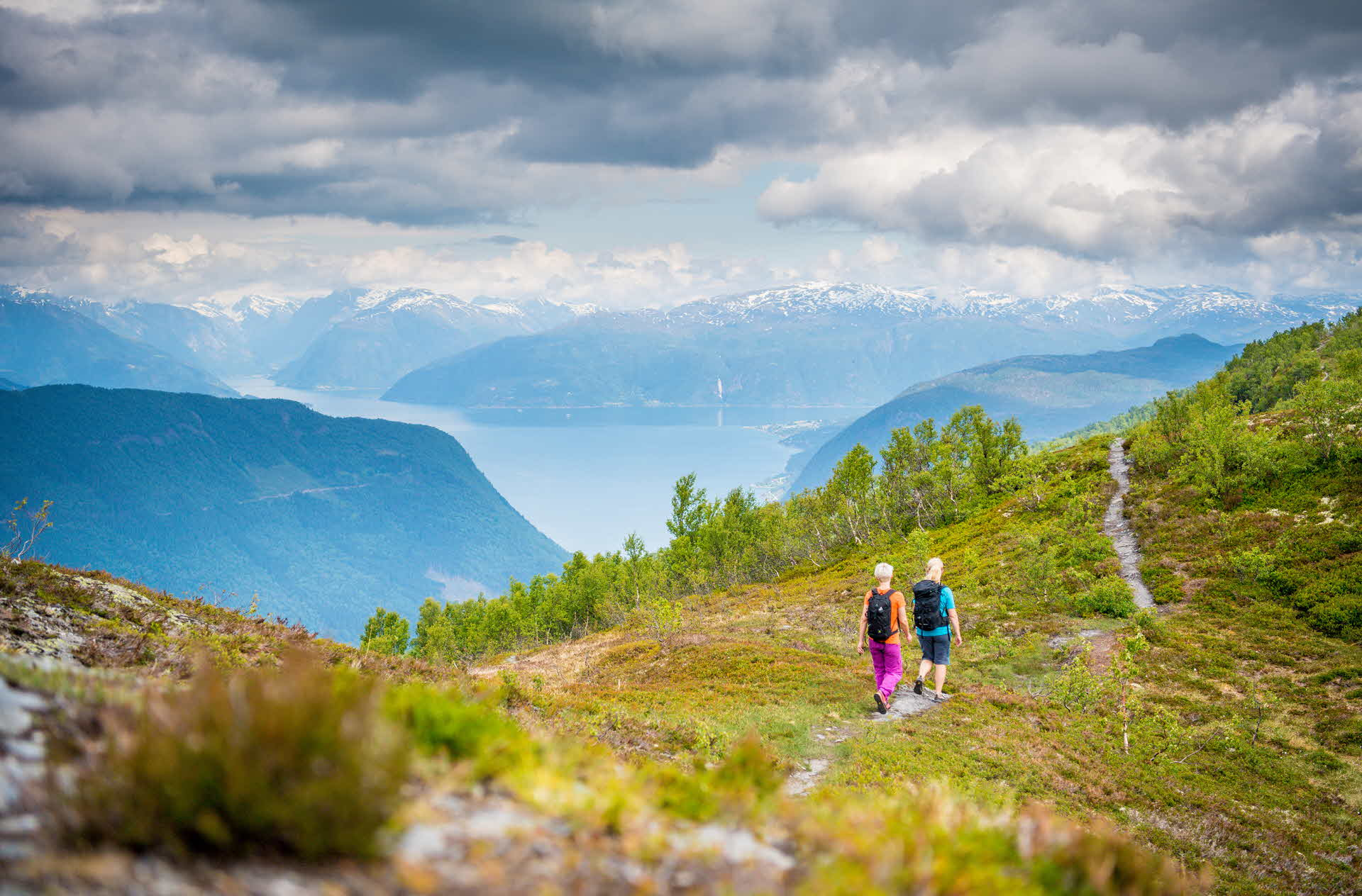 Two people walking along a path on Vikafjell with a view of