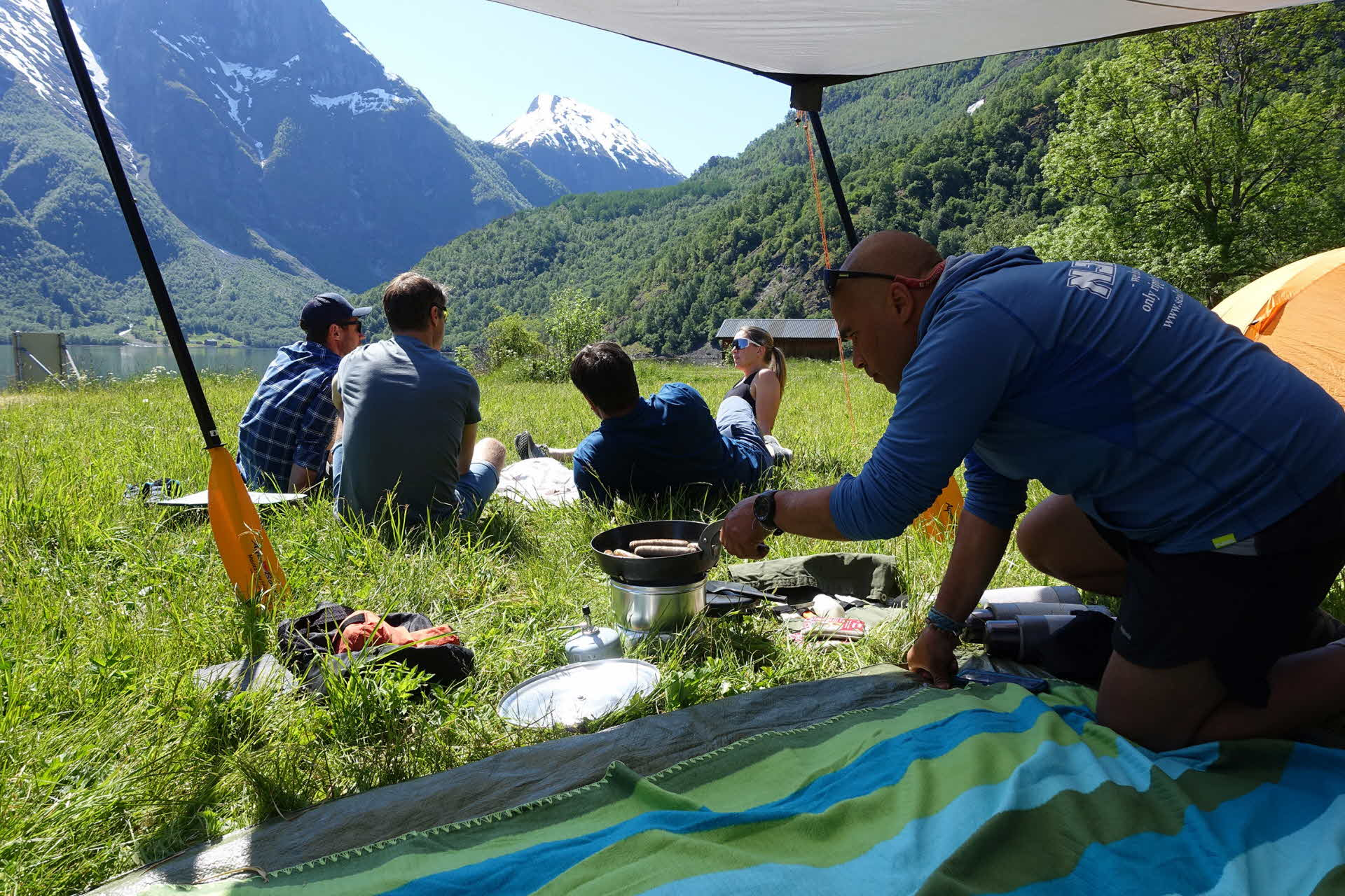 4 people relaxing in sun in green meadow by UNESCO Naeroyfjord while another is preparing food under sun sail